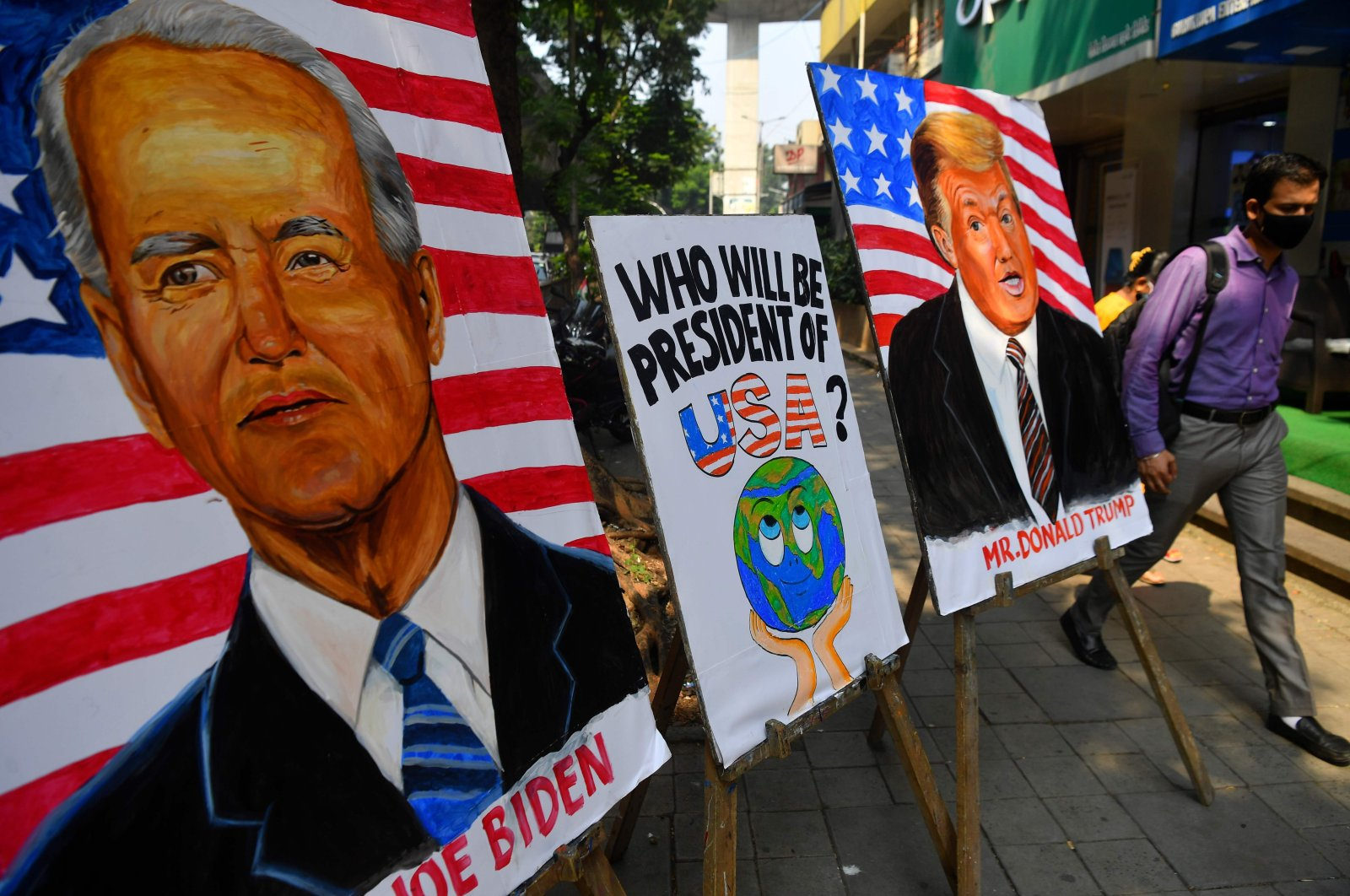 A commuter walks past the painted images of U.S. President Donald Trump and Democratic presidential candidate and former Vice President Joe Biden ahead of the upcoming U.S. presidential elections, outside an art school in Mumbai, India, Oct. 29, 2020. (AFP)