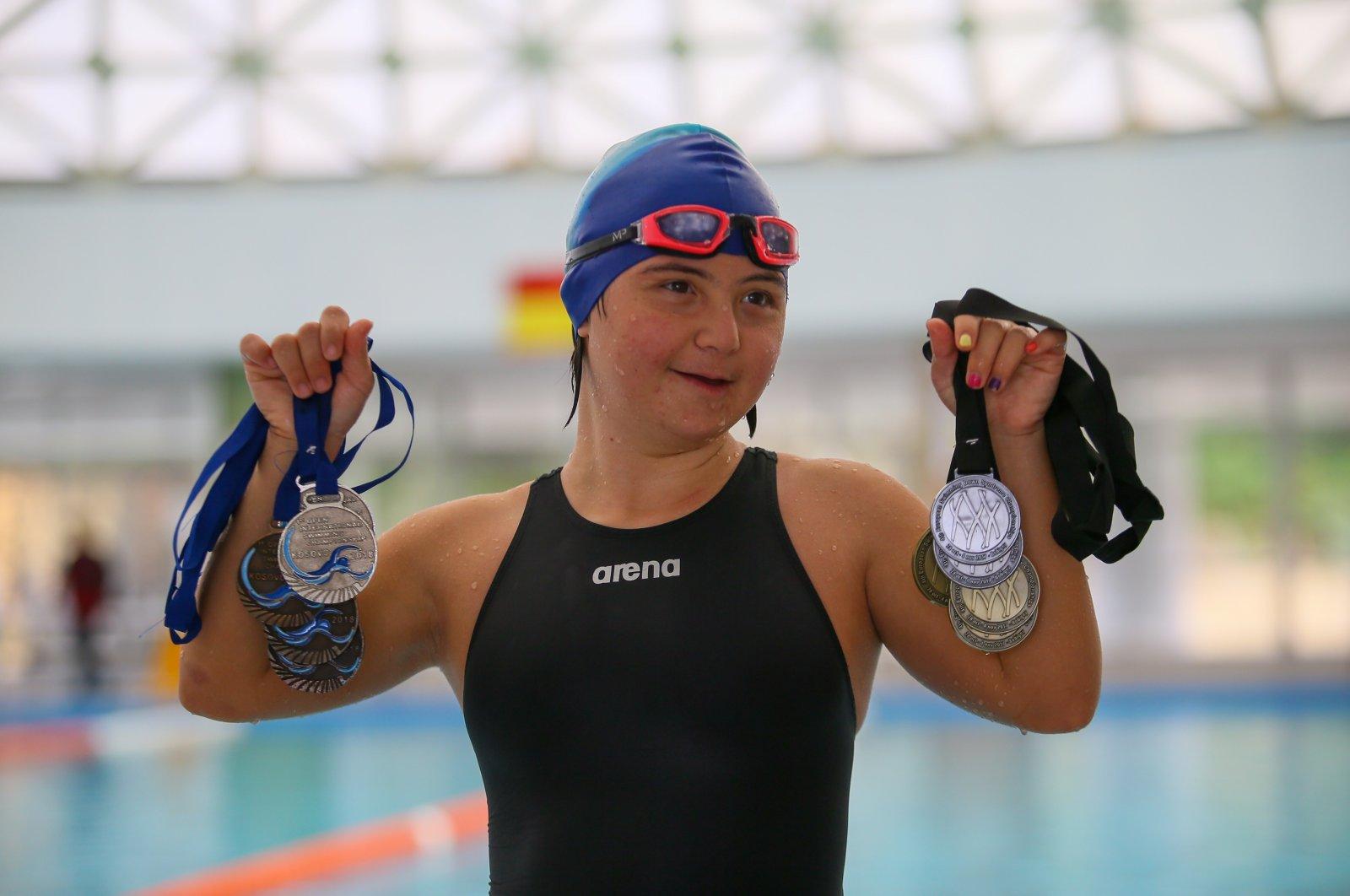 Irem Öztekin poses with her medals at an indoor pool, in Izmir, Turkey, Oct. 30, 2020. (AA Photo)