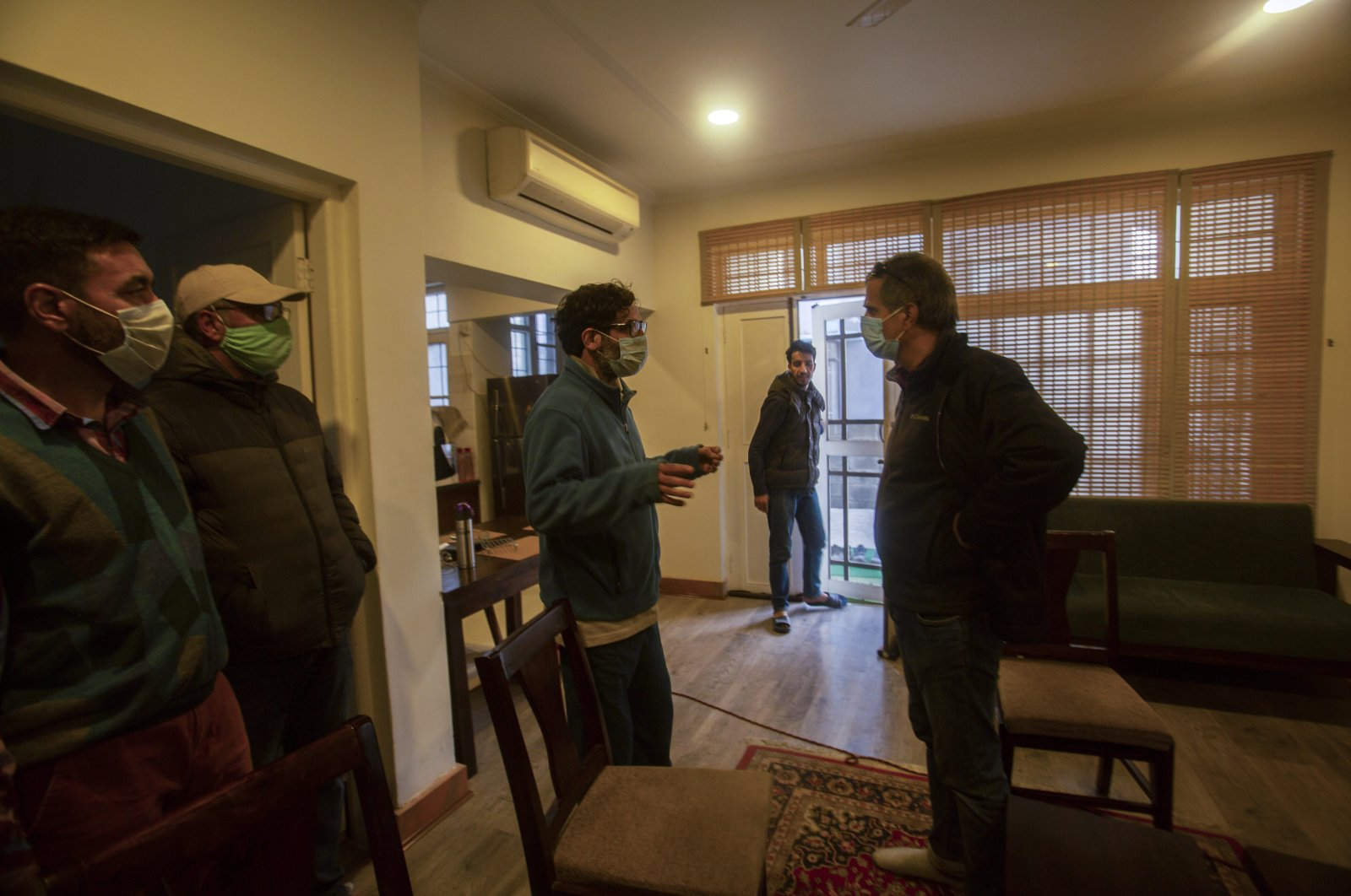 Agence France-Presse's Kashmir correspondent Parvaiz Bukhari (C), talks to his colleagues after National Investigation Agency personnel searched his premises on the outskirts of Srinagar, Indian controlled Kashmir, Oct. 28, 2020. (AP Photo)