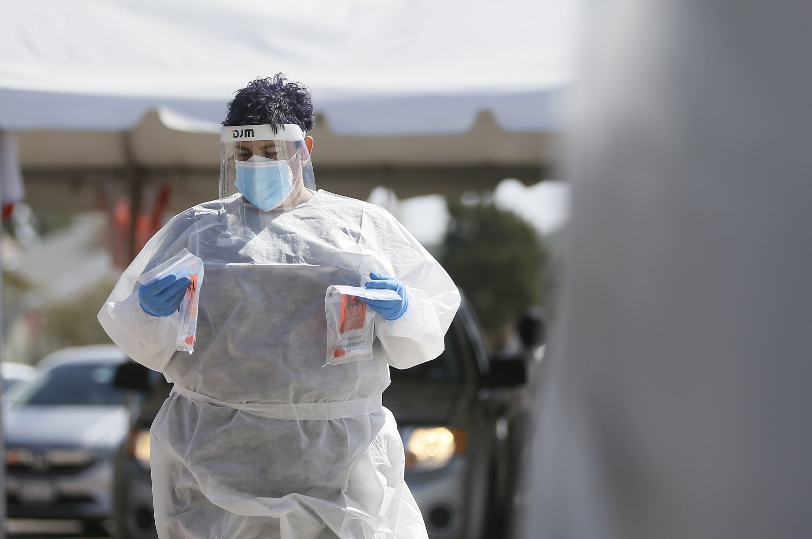 A medical worker takes COVID-19 swabs in for testing at the state drive-thru testing location UTEP Monday, Oct. 26, 2020 in El Paso, Texas. (The El Paso Times via AP)