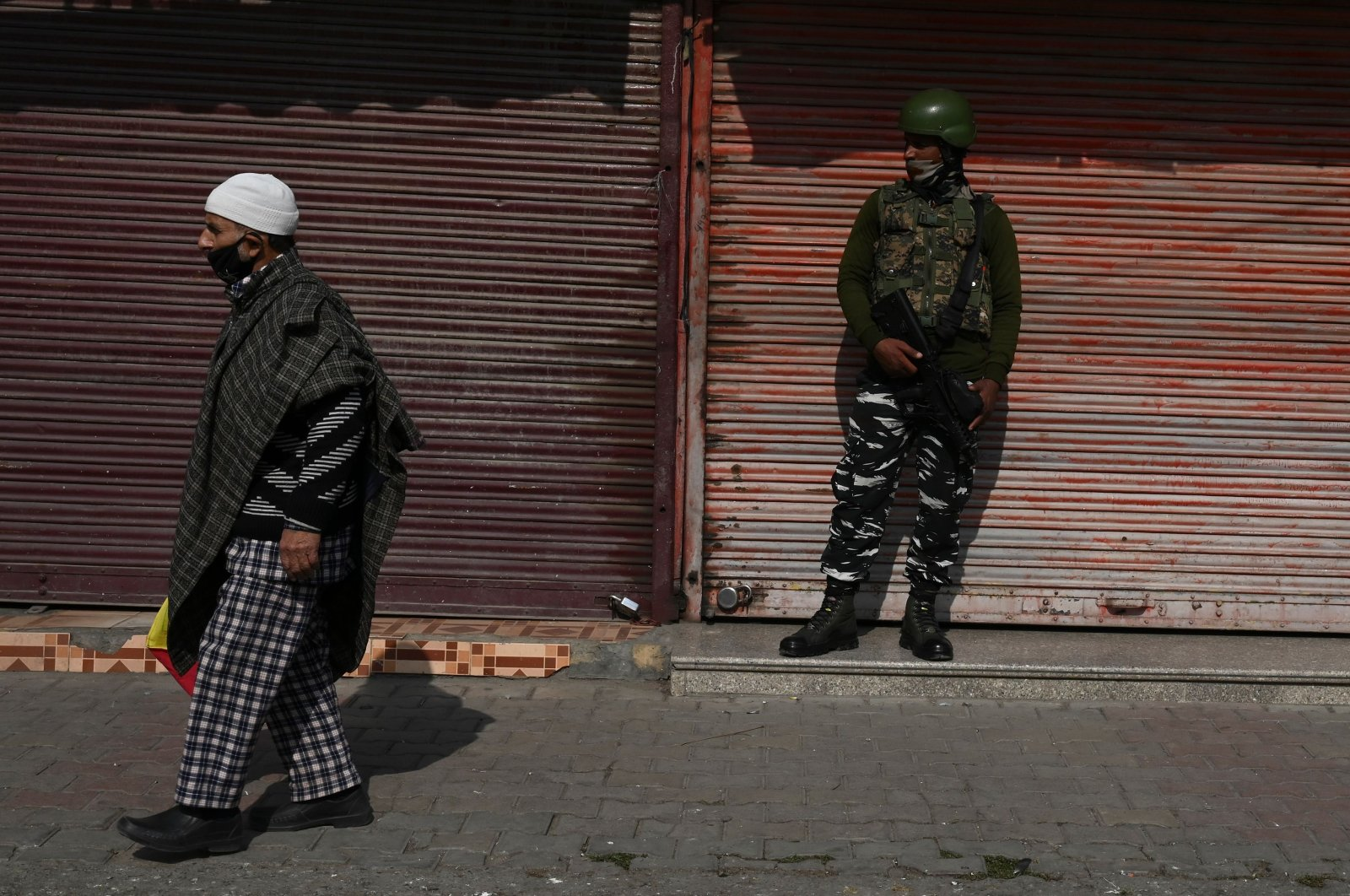 A resident walks past an Indian army soldier standing guard next to closed shops during a one-day strike called by the All Parties Hurriyat Conference (APHC) against the Indian government's decision to open Kashmir land for all Indians, in Srinagar on Oct. 31, 2020. (AFP Photo)