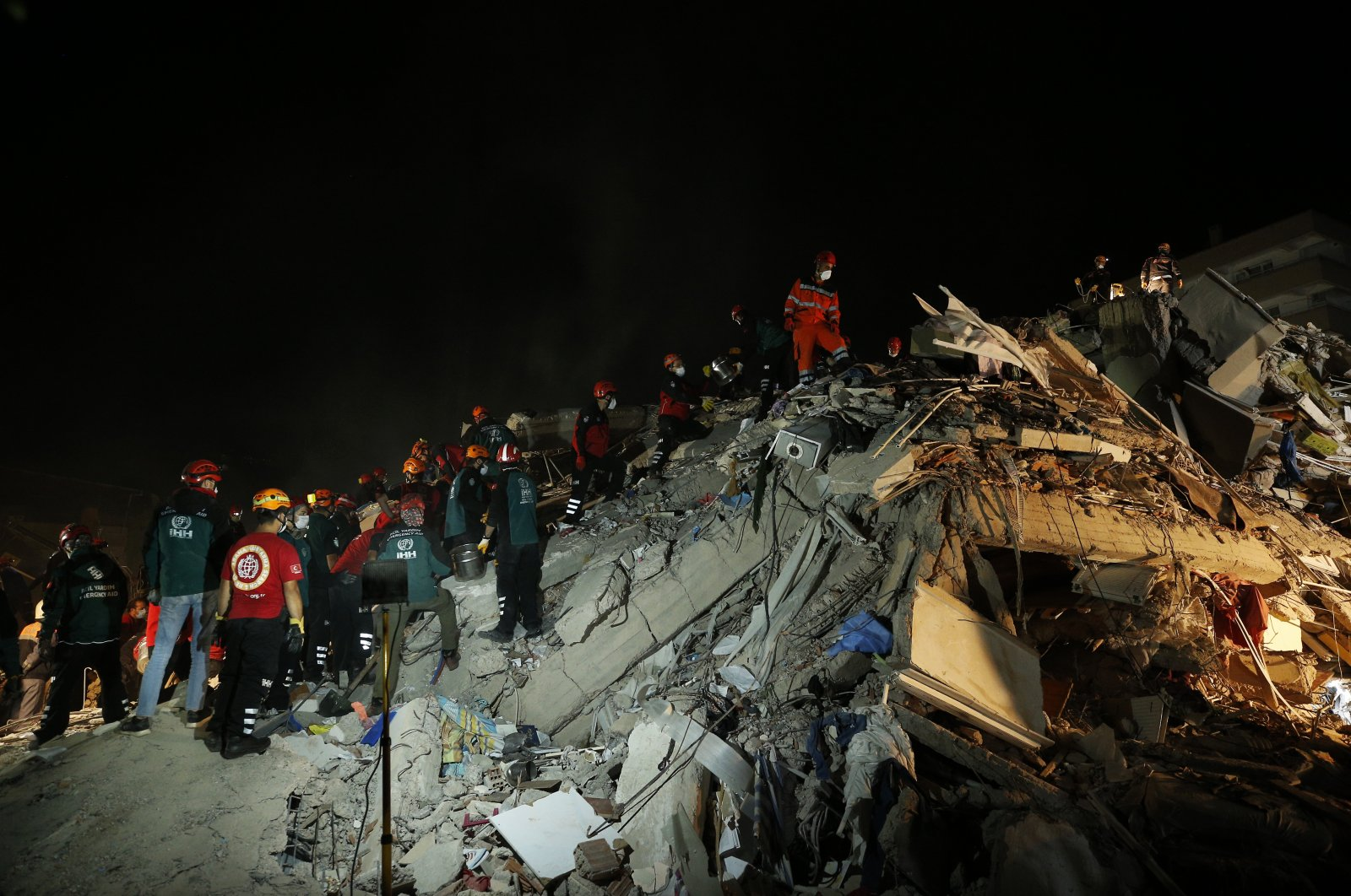 Members of rescue services search in the debris of a collapsed building for survivors in Izmir, Turkey, early Saturday, Oct. 31, 2020. (AP Photo)
