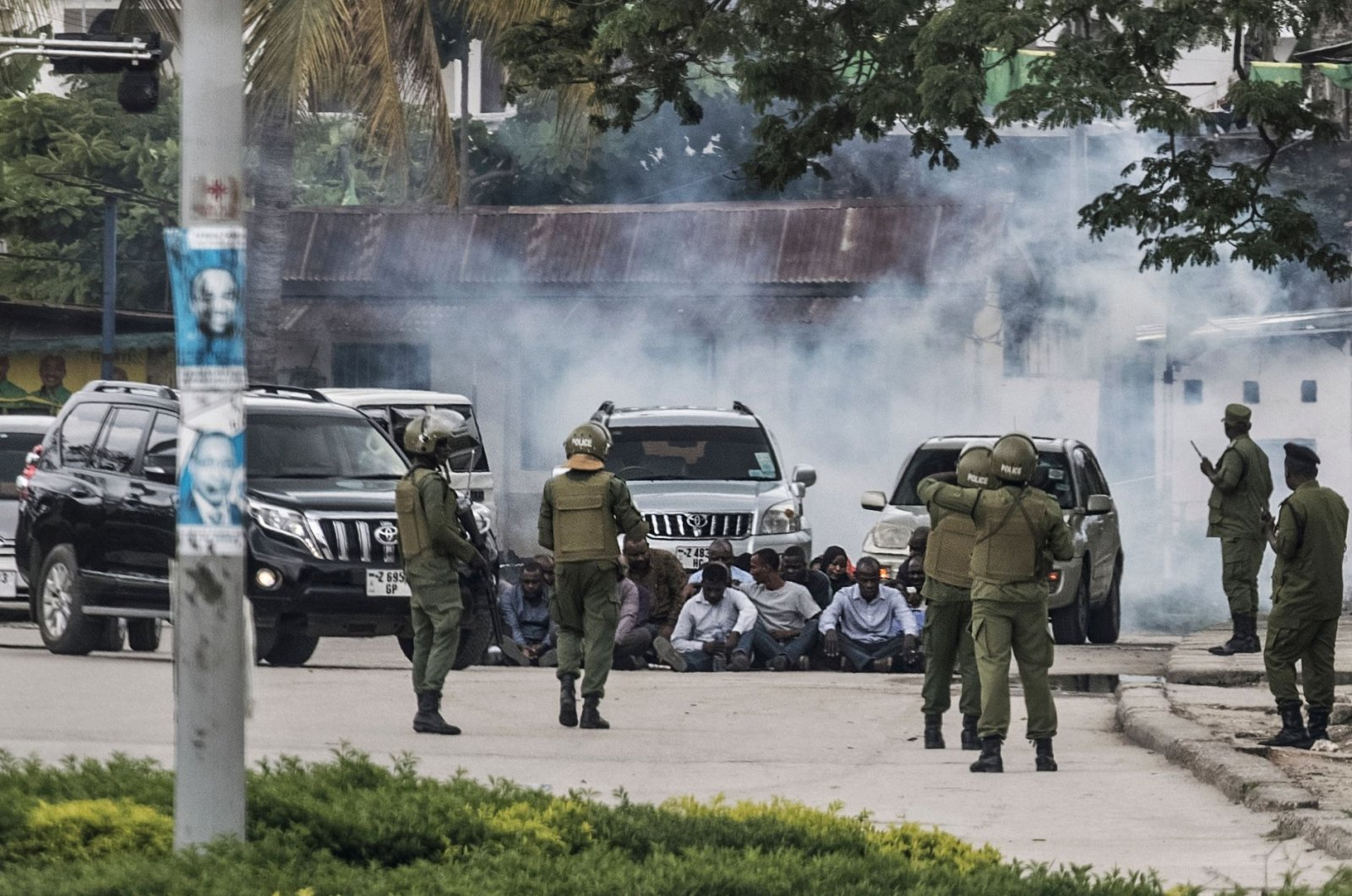 Zanzibar's anti-riot police officers stand guard by a group of men sitting on the ground during an operation after the opposition called for protests in Stone Town, on Oct. 29, 2020. (AFP Photo)
