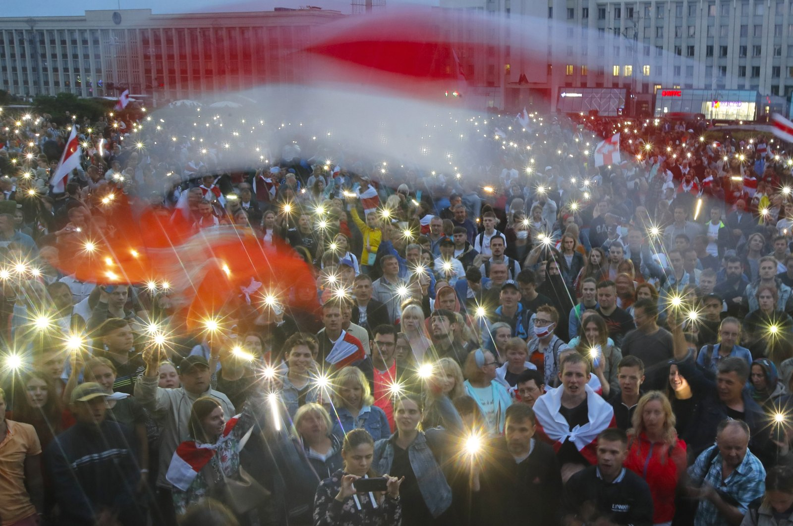 Belarusian opposition supporters light their phones and wave an old Belarusian national flag during a protest rally in front of the government building at Independent Square in Minsk, Belarus, Aug. 19, 2020. (AP Photo)