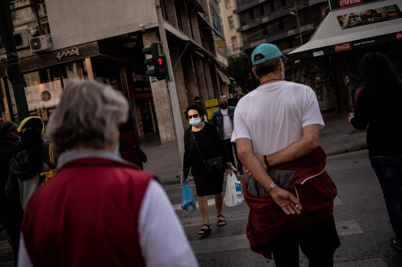 People, wearing protective face masks, walk in Athens' main commercial district on Oct. 30, 2020. (AFP Photo)