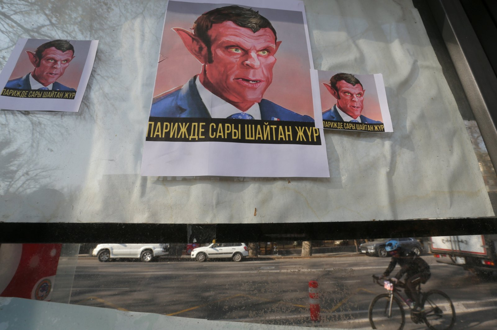 "Placards reading ""The yellow Devil is in Paris"" hang in a window as a mark of a protest against the publications of a cartoon of Prophet Muhammad in France and French President Emmanuel Macron's comments, in Almaty, Kazakhstan on Oct. 31, 2020. (Reuters Photo)"