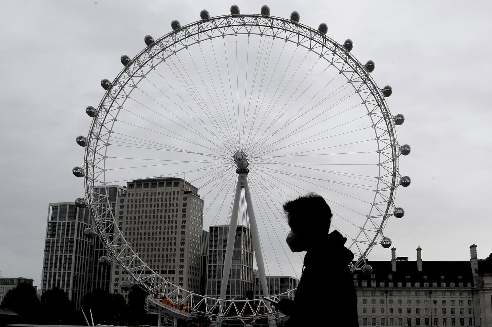 A man wears a face mask as he passes the London Eye in London, Oct. 29, 2020. (AP Photo)