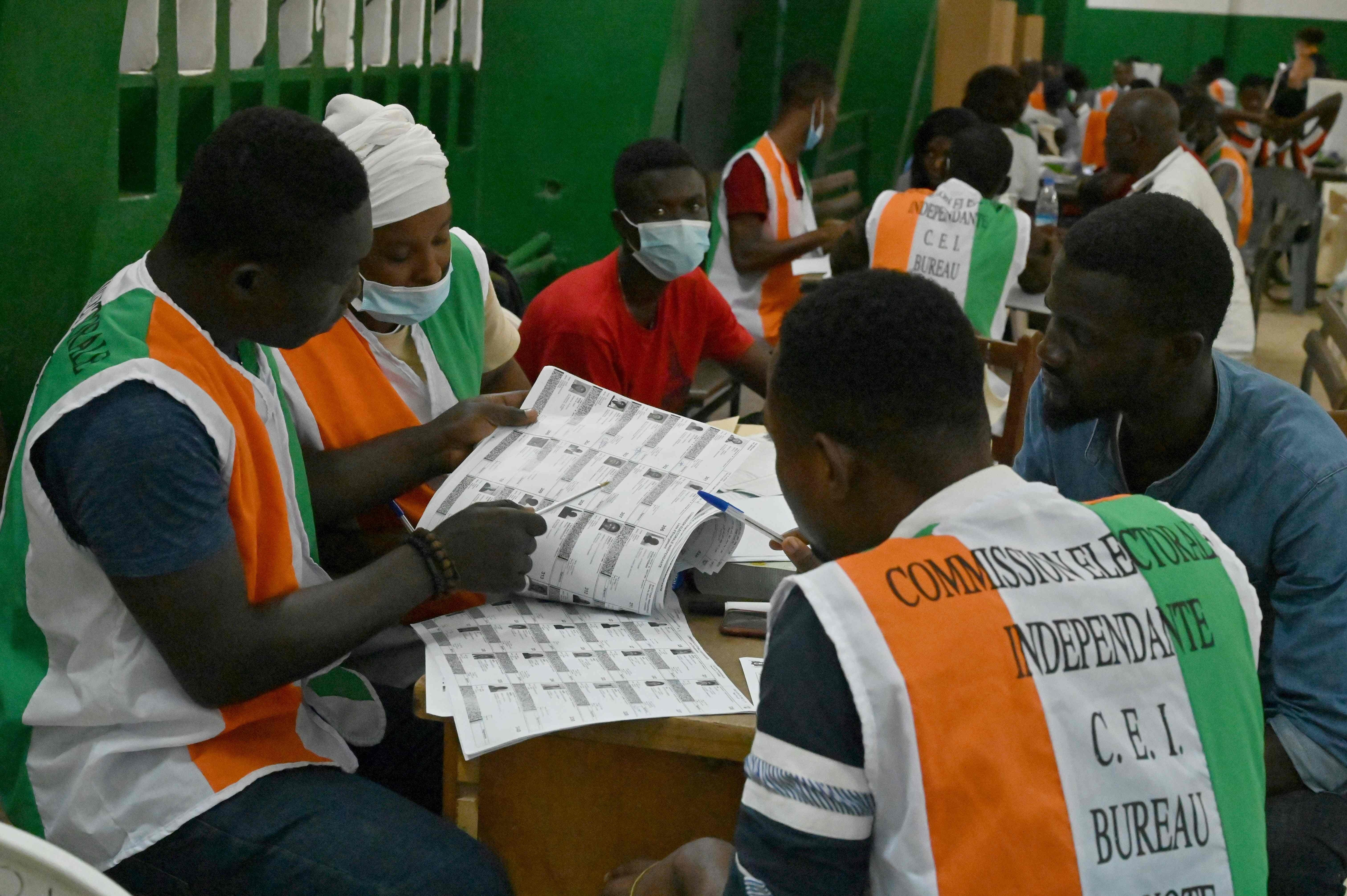 Electoral commission officials check the voter's roll as they count votes for Ivory Coast's presidential election at a polling station in Abidjan, Ivory Coast, Oct. 31, 2020. (AFP Photo)
