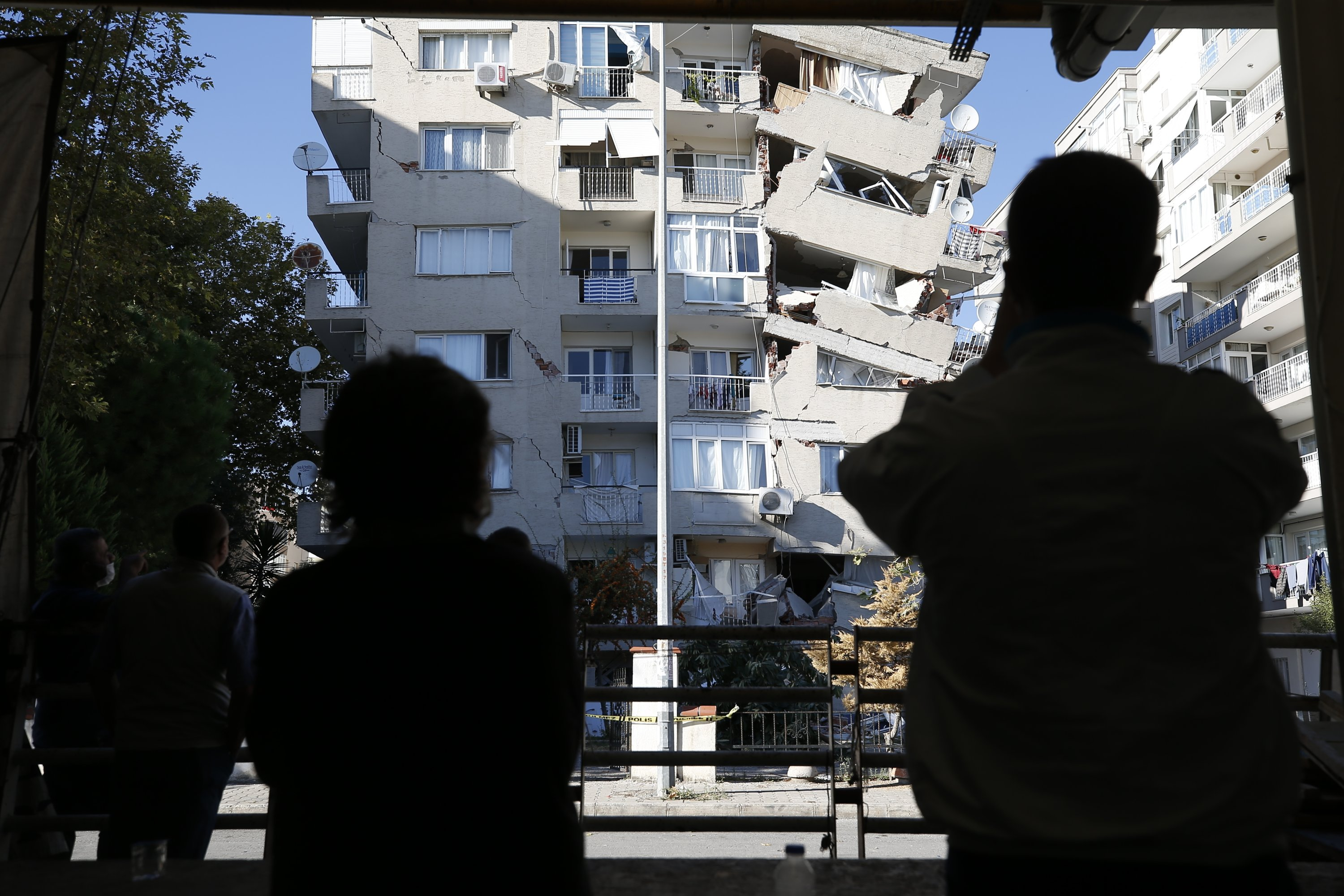 Local residents look at a heavily damaged building in Izmir, Turkey, Oct. 31, 2020. (AP Photo)