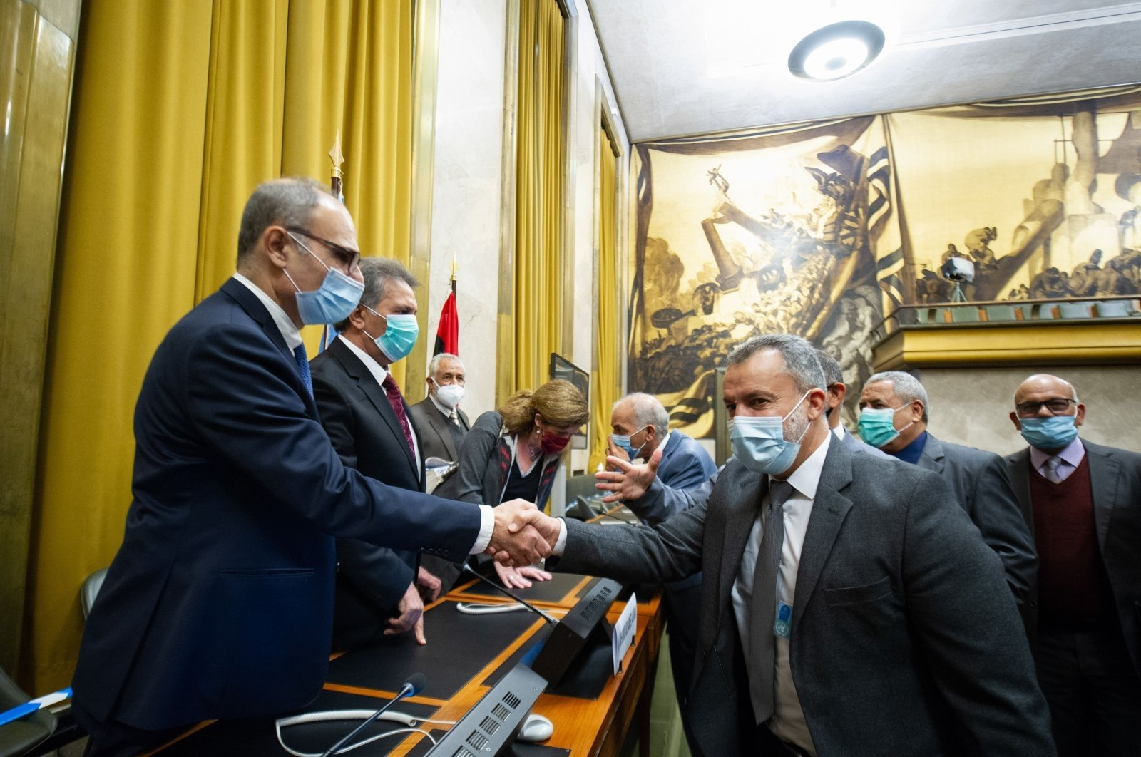 Representatives of Libya's two rival factions shake hands after a signing ceremony, on Oct. 23, 2020. (AFP Photo)