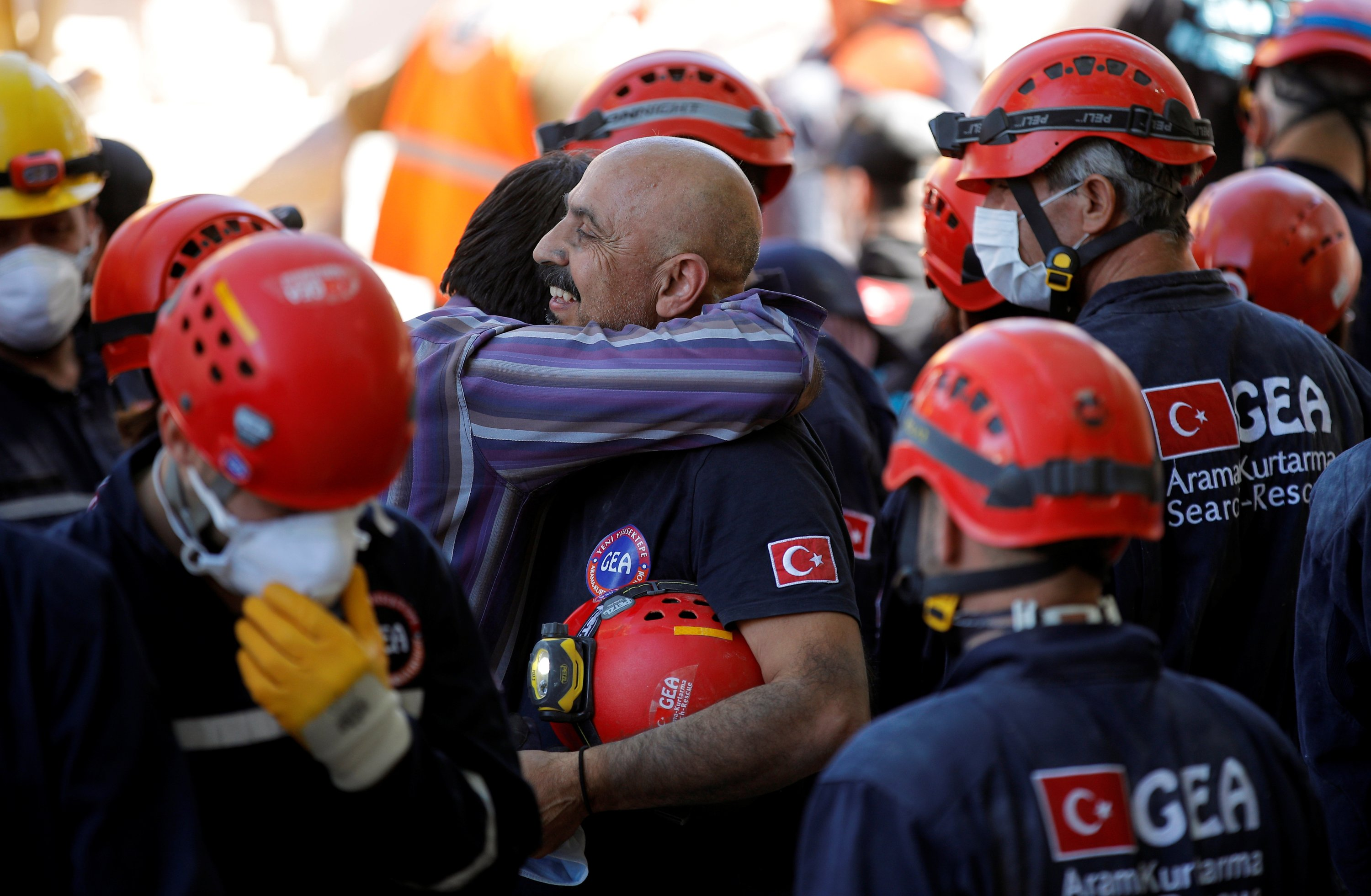 A survivor hugs rescue personnel after learning his family was pulled out alive from under the debris, in Izmir, Turkey, Oct. 31. (Reuters Photo)