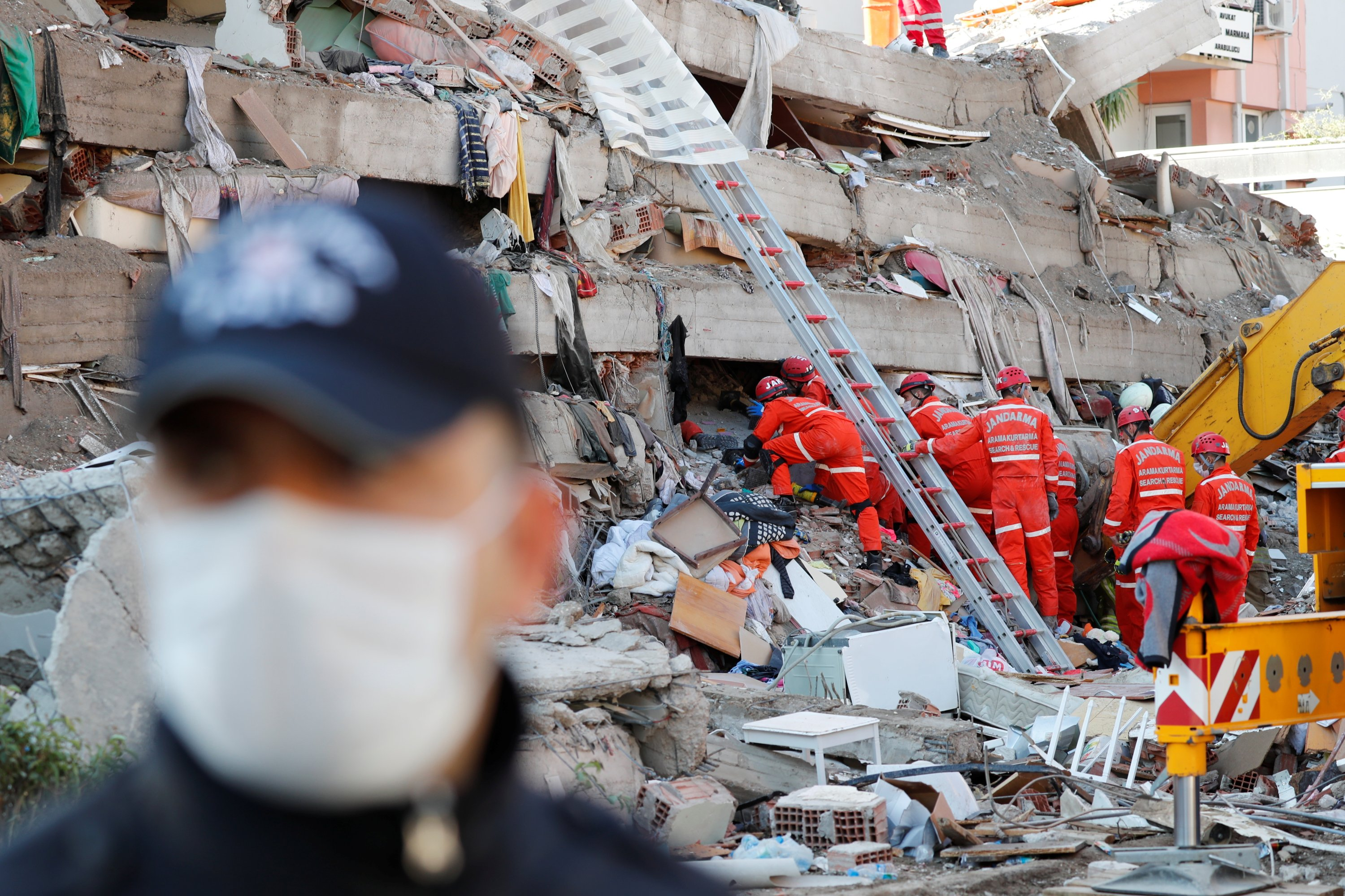 A police officer stands as rescue teams continue search efforts among the rubble, in Izmir, Turkey, Oct. 31, 2020. (Reuters Photo)