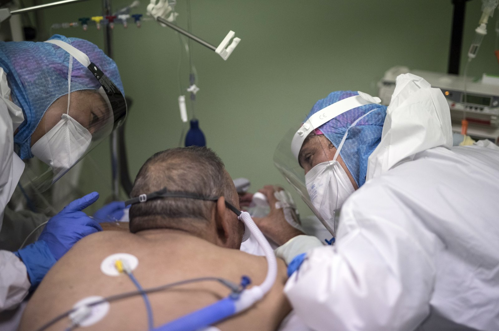 Nurses comfort a COVID-19 patient in the intensive care unit at the Joseph Imbert Hospital Center in Arles, southern France, Oct. 28, 2020. (AP Photo)