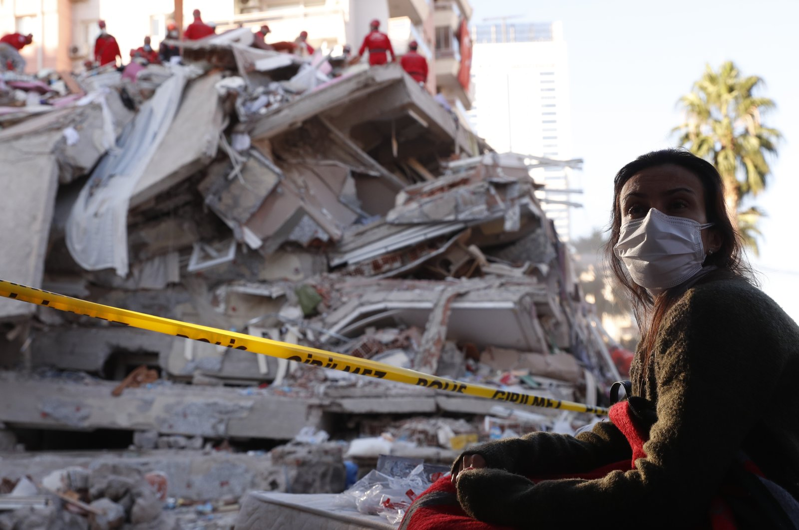 A local resident watches as rescue teams search for survivors in the debris of a collapsed building in Izmir, Turkey, Oct. 31, 2020. (AP Photo)