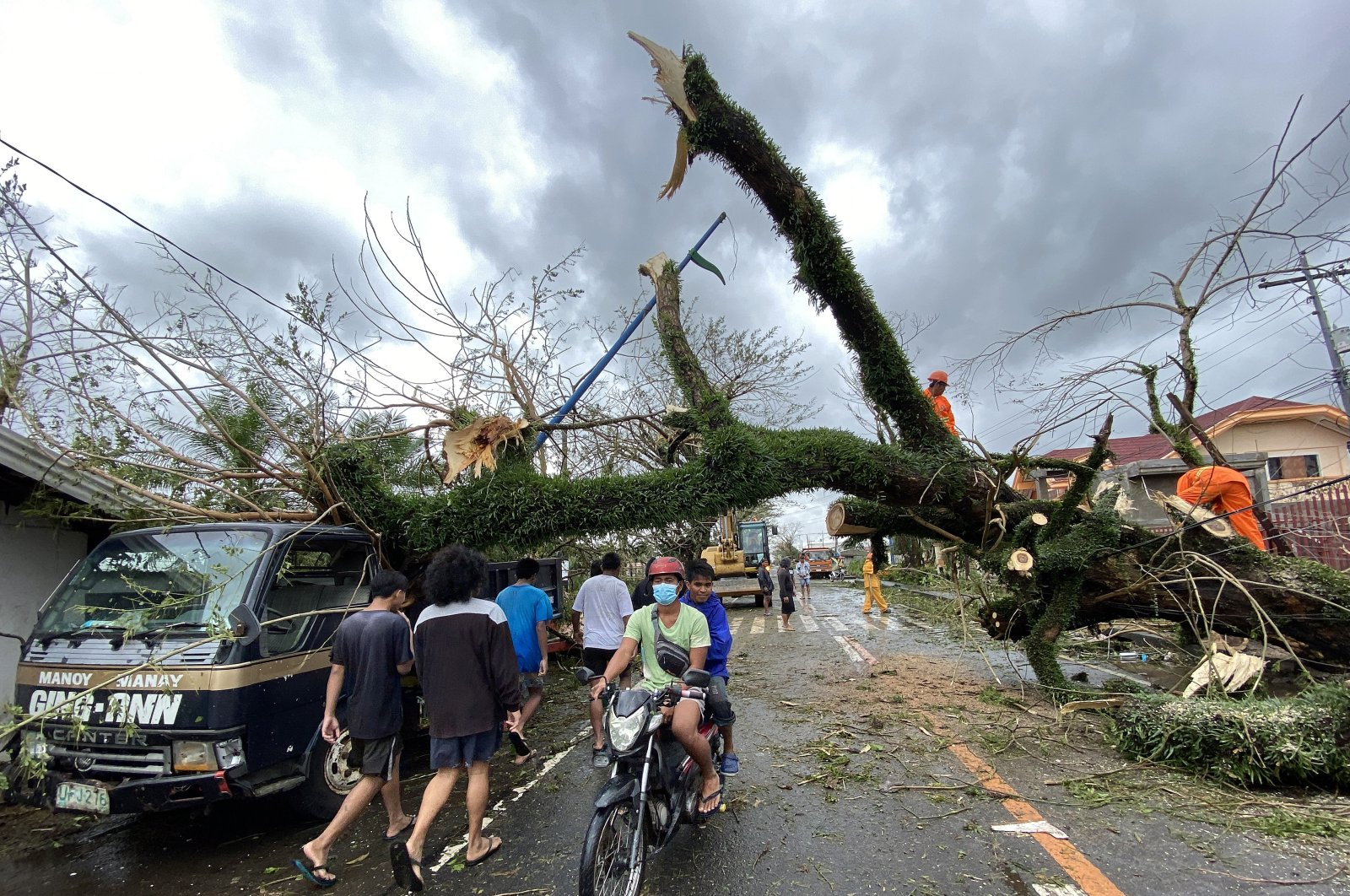 Filipino villagers maneuver under a toppled tree in the typhoon-hit town of Tigaon, Camarines Sur, Philippines, 01 November 2020. Super Typhoon Goni, with winds forecasted to reach 249 kilometers per hour, made landfall in the provinces of Albay and Camarines sur, according to the local weather bureau. (EPA Photo)