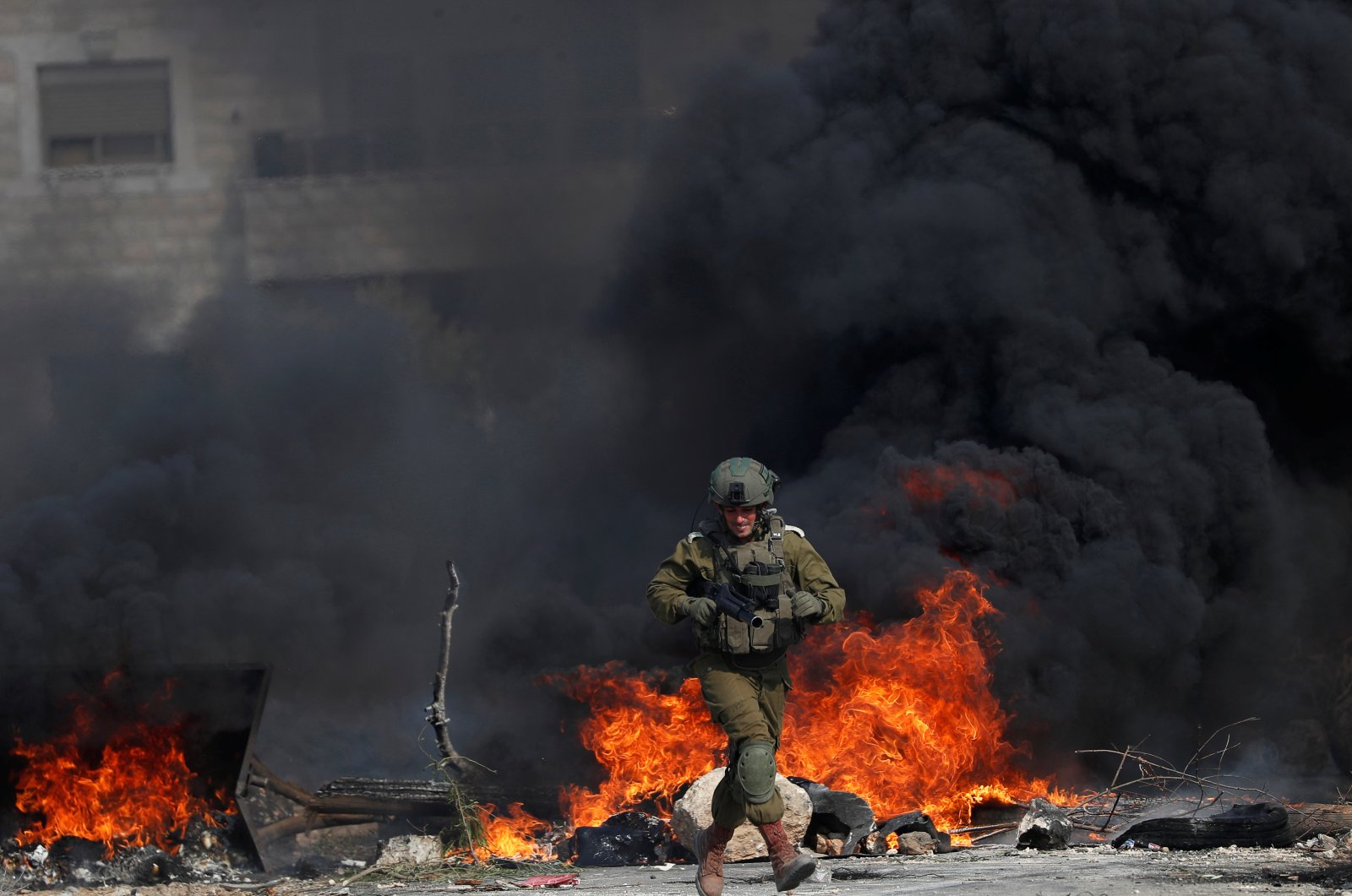 An Israeli soldier runs in front of burning tires during a Palestinian protest against Jewish settlements, in Beit Dajan in the Israeli-occupied West Bank, Oct. 30, 2020. (Reuters Photo)