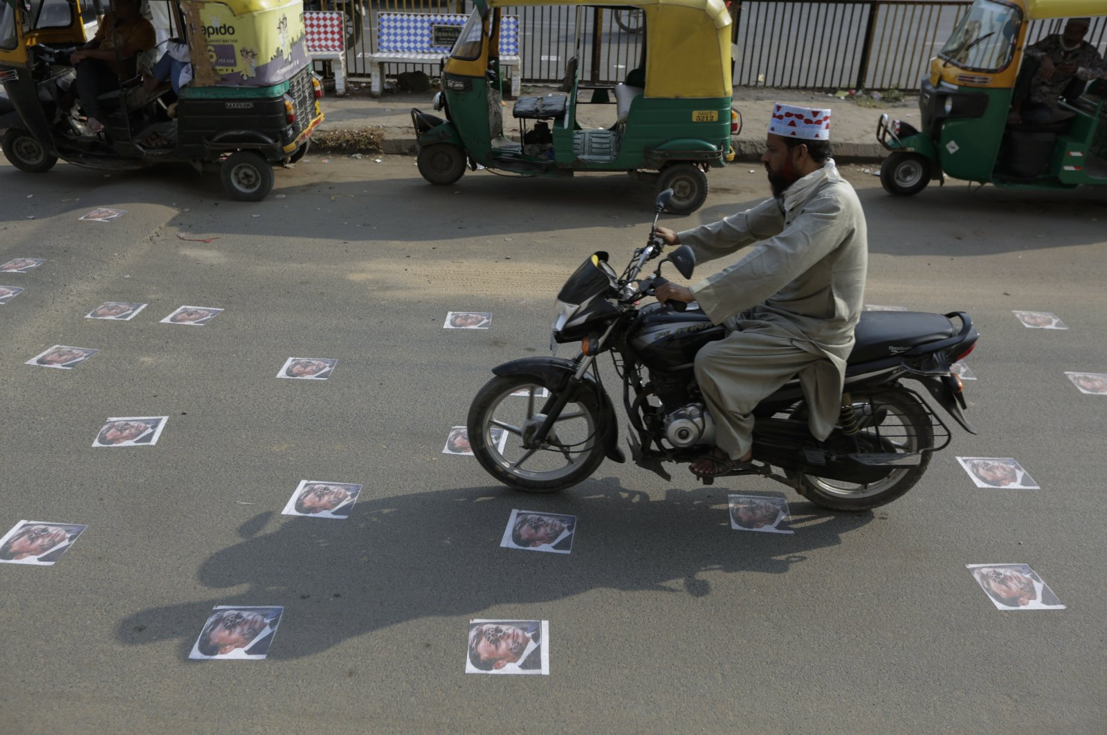 An Indian commuter drives over defaced images of French President Emmanuel Macron pasted on a road by protestors in Ahmedabad, India, Nov. 1, 2020. (AP Photo)