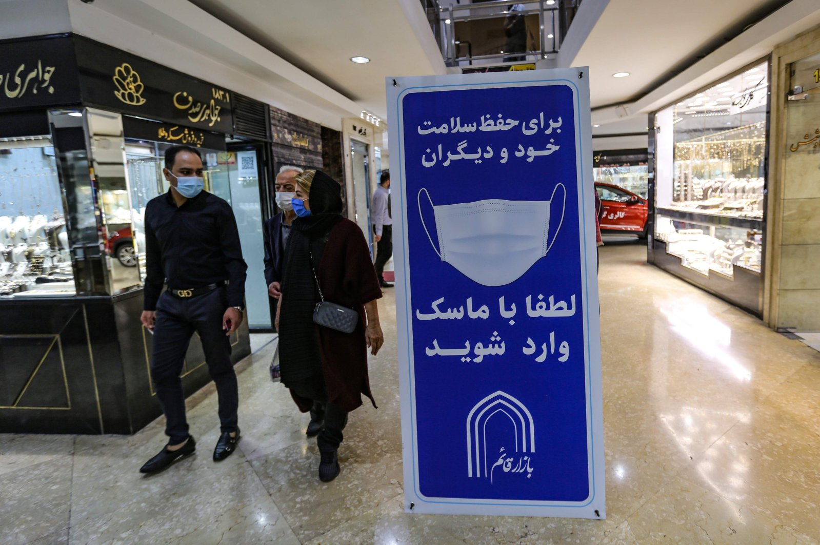 Iranians walk next to a sign advising people to wear masks on their way to shop in Tajrish square in the capital Tehran on Nov. 1, 2020, amid the COVID-19 pandemic crisis. (AFP Photo)
