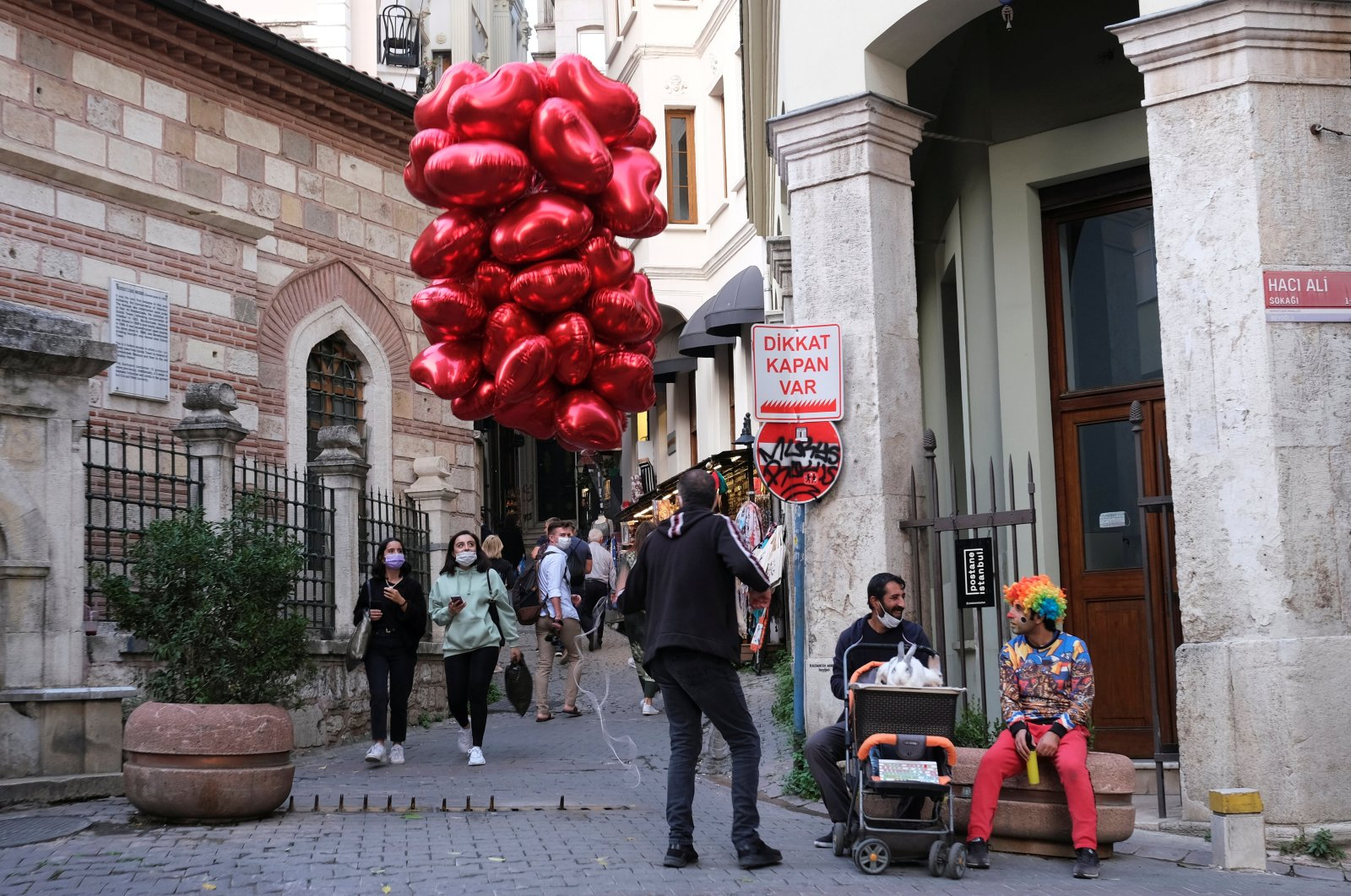 People wearing protective face masks look at a street vendor selling heart-shaped balloons, as the coronavirus disease (COVID-19) outbreak continues, in Istanbul, Turkey October 27, 2020. (Reuters Photo)