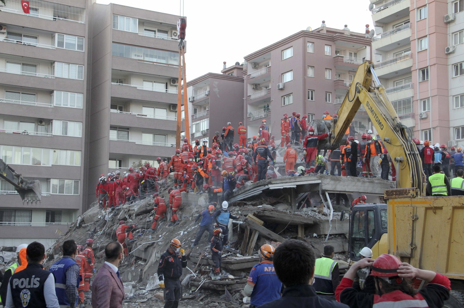 Rescue workers, who were trying to reach survivors in the rubble of a collapsed building, leave the area as the adjacent building at the right started moving, in Izmir, Turkey, Nov. 1, 2020. (AP Photo)