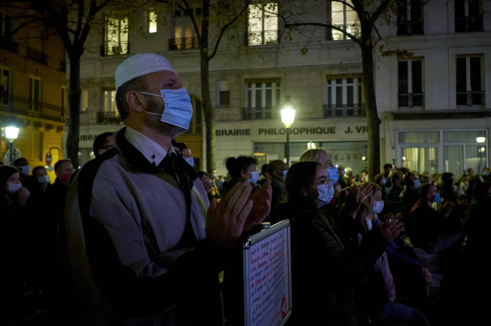 People gather on the Place de la Sorbonne to watch a live broadcast on a giant screen of the national tribute to the French history teacher Samuel Paty, who was killed in a terrorist attack, in the capital Paris, France, Oct. 21, 2020. (Photo by Getty Images)
