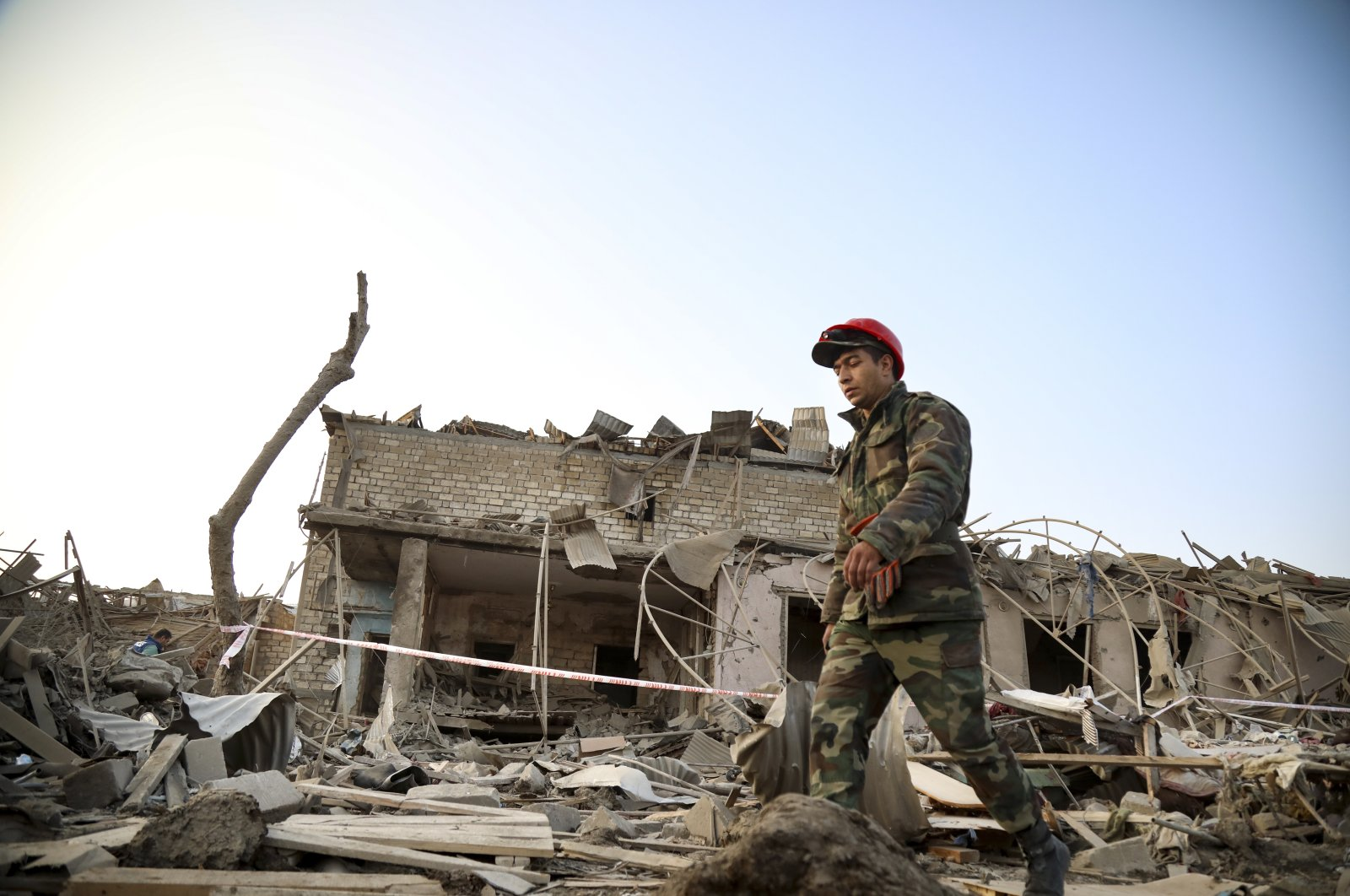 A soldier walks past a destroyed house in a residential area of Azerbaijan's second-largest city that was hit by rocket fire overnight by Armenian forces, Ganja, Azerbaijan, Oct. 17, 2020. (AP Photo)