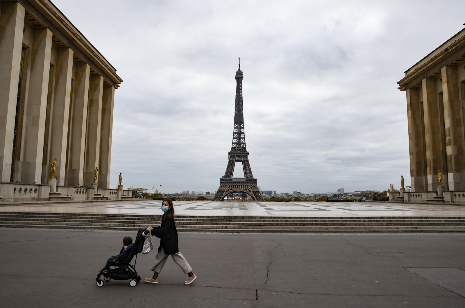 A woman pushes a stroller across a deserted Trocadero Square near the Eiffel Tower on the first morning of the second national lockdown, Paris, Oct. 30, 2020. (EPA Photo)