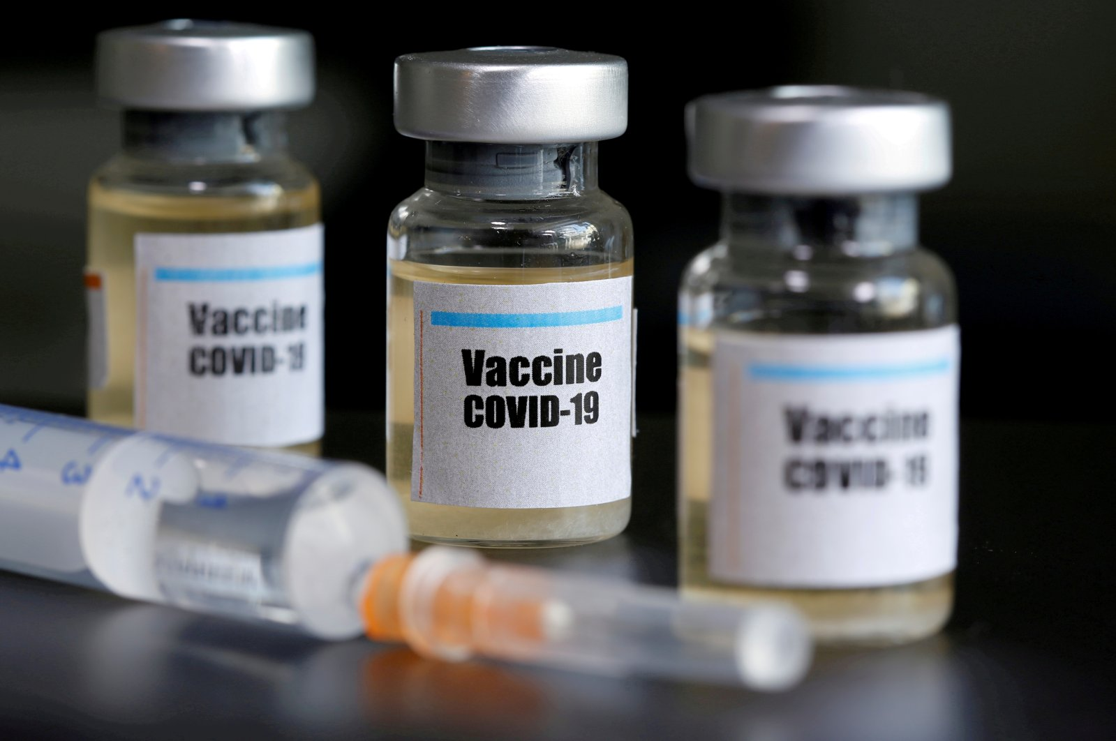 """Small bottles labeled with a """"Vaccine COVID-19"""" sticker and a medical syringe are seen in this illustration taken taken, April 10, 2020. (Reuters Photo)"""