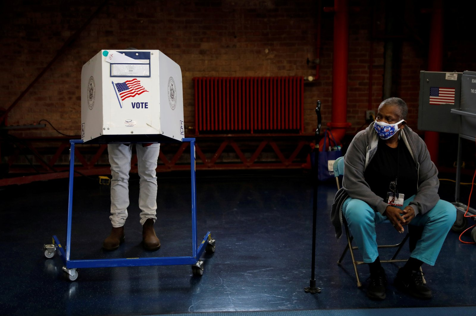 An election volunteer stands by as a voter fills out a ballot in a booth during early voting in the Brooklyn borough of New York City, Oct. 27, 2020. (Reuters Photo)