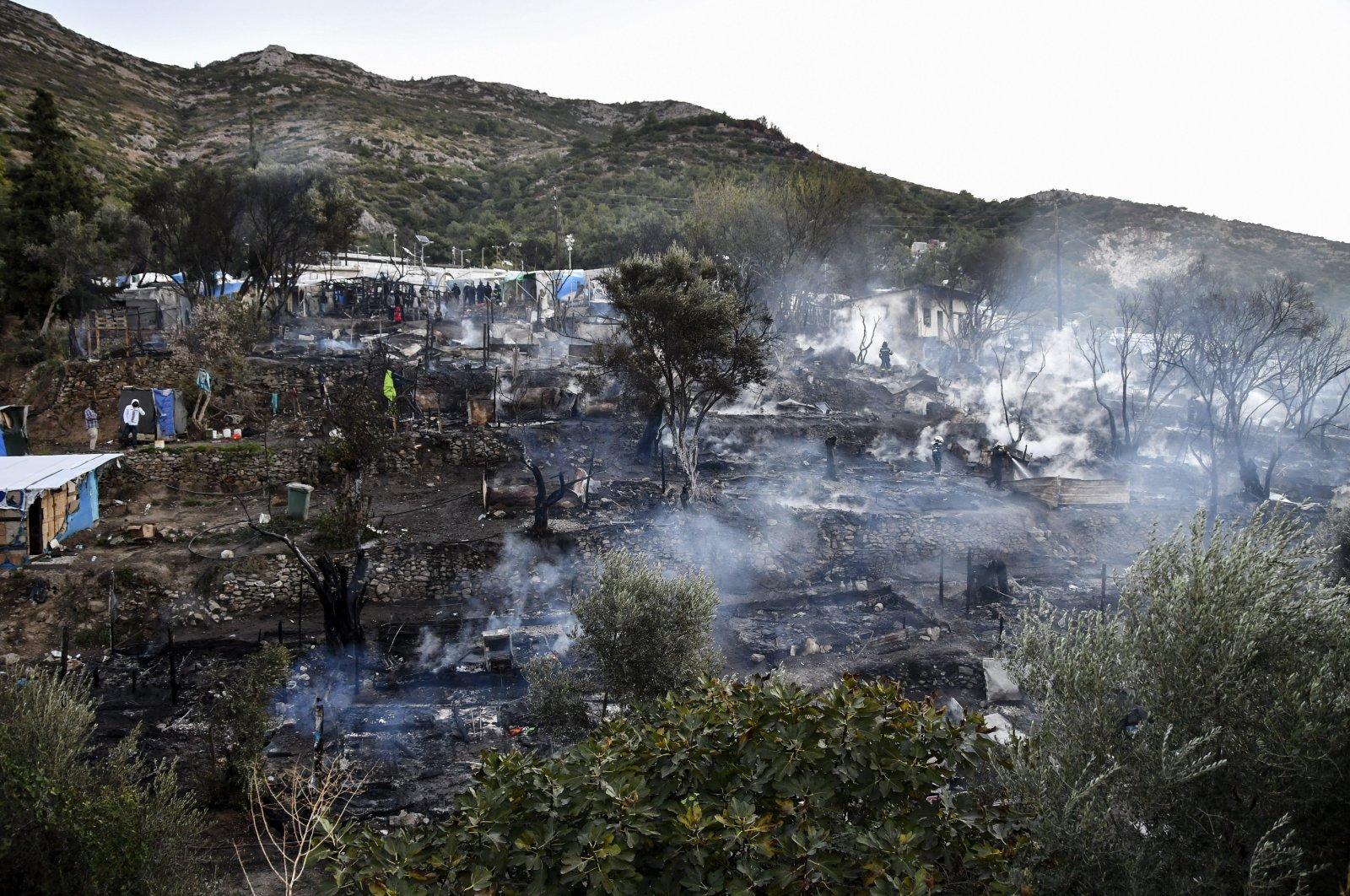 Smoke billows from a refugee and migrant camp after a fire broke out on the Greek island of Samos, Greece, Nov. 2, 2020. (AP Photo)