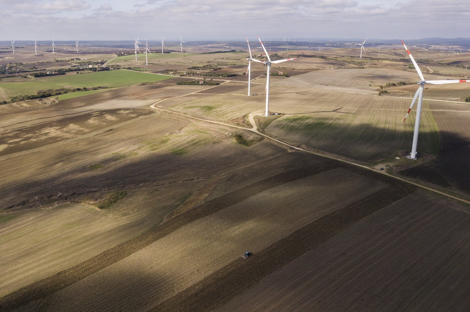 An aerial picture taken with a drone shows a Turkish farmer plows his farmland with a tractor in front of wind turbines at the country side of Istanbul, Turkey, Oct. 22, 2020.  (EPA Photo)