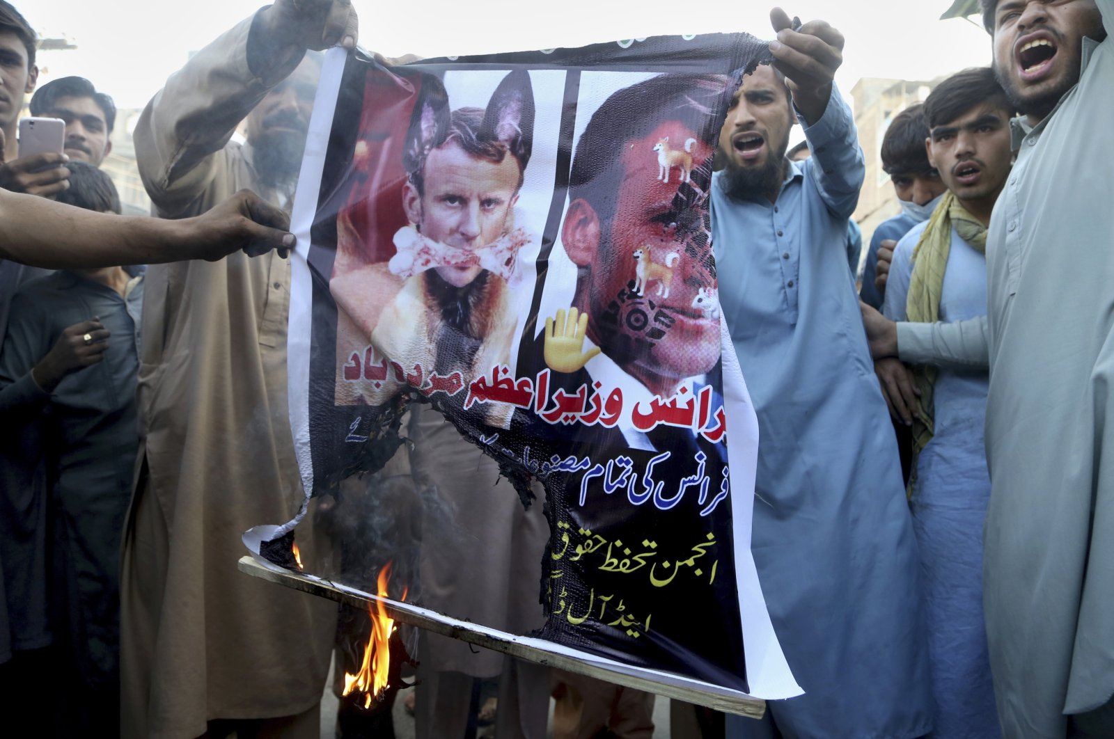 Traders burn defaced images of Emmanuel Macron during a protest against the French president and the republication of caricatures in France of the Prophet Muhammad, in Peshawar, Pakistan, Nov. 2, 2020. (AP Photo)