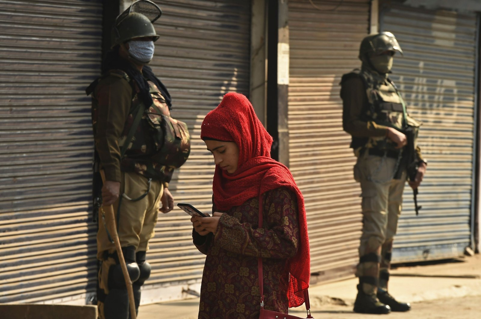 A resident walks past Indian army soldiers standing guard next to closed shops during a one-day strike called by the All Parties Hurriyat Conference (APHC) against the Indian government's decision to open Kashmir land for all Indians, in Srinagar, Jammu and Kashmir, India, Oct. 31, 2020. (AFP Photo)