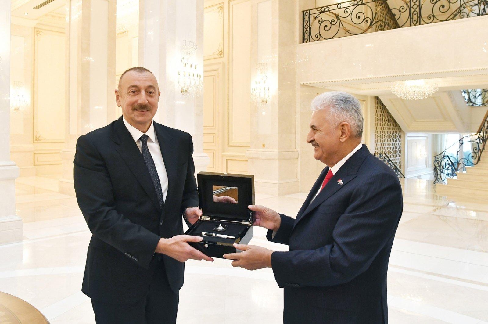 Azerbaijan's President Ilham Aliyev presents a gift to the ruling Justice and Development Party's (AK Party) deputy Binali Yıldırım in the capital Baku, Nov. 2, 2020. (AA Photo)