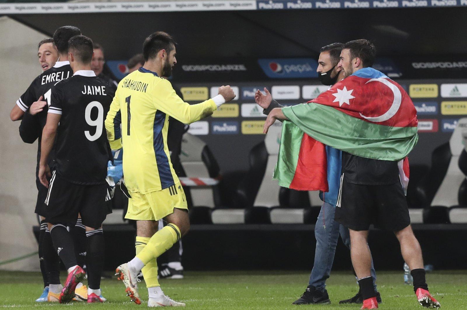 Qarabag's Qara Qarayev, with an Azerbaijani flag, and his team celebrates after the Europa League football match between Legia Warsaw and Qarabag, in Warsaw, Poland, Oct. 1, 2020. (AP Photo)