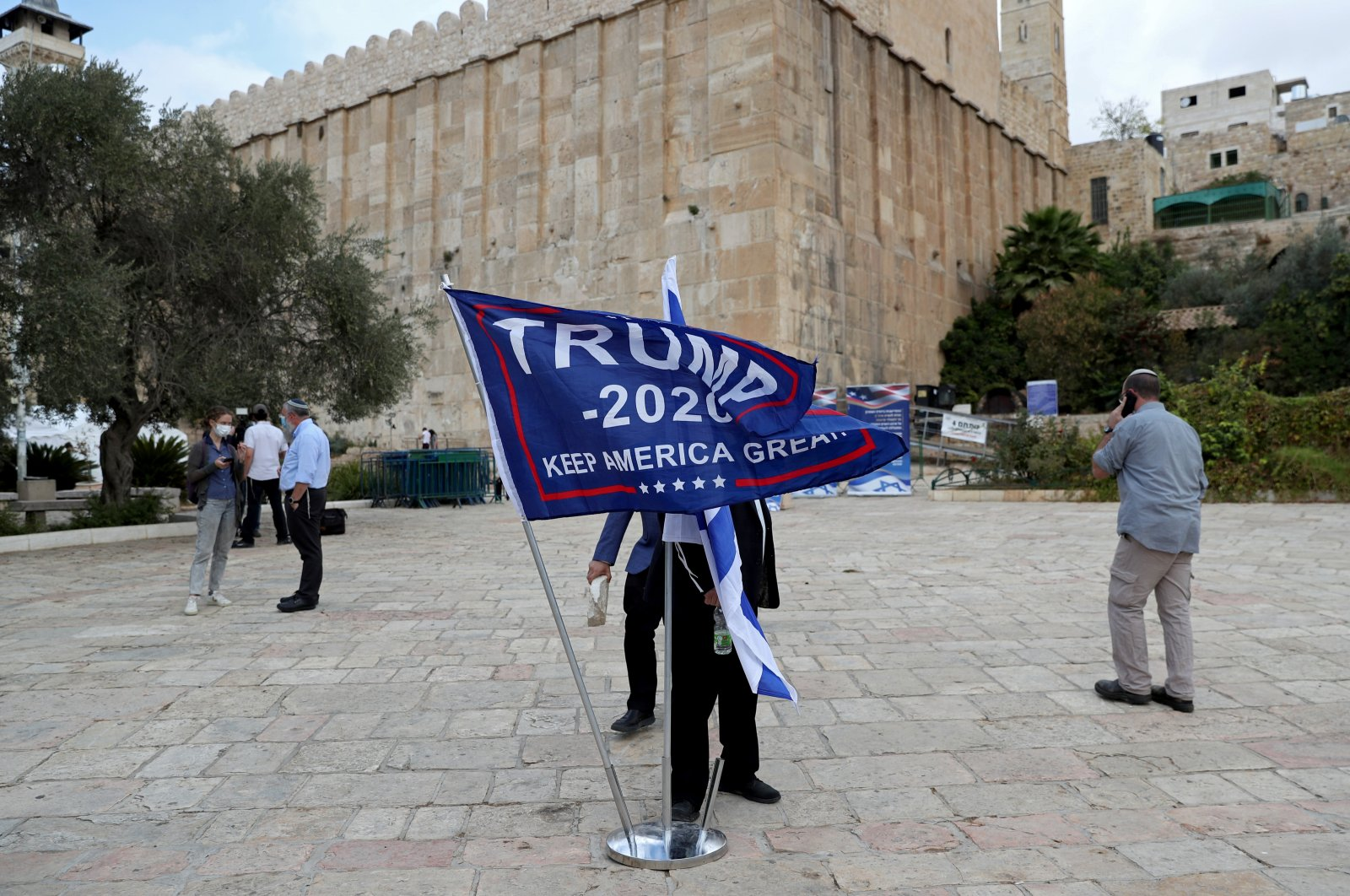An Israeli settler adjusts a flag during a gathering to show support for U.S. President Donald Trump in the Israeli-occupied West Bank, Palestine, Nov. 2, 2020. (Reuters Photo)
