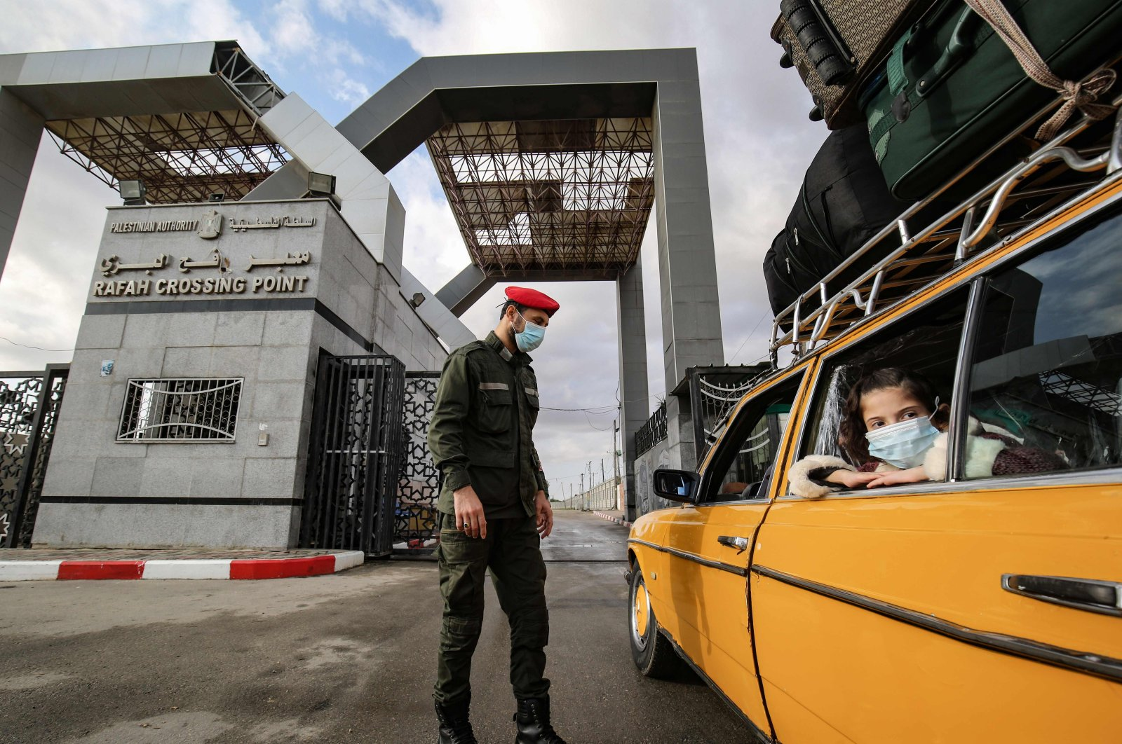 A Palestinian border guard, wearing protective face masks due to the COVID-19 pandemic, checks the ID of travelers as they wait their turn to cross into Egypt through the Rafah border crossing from the Gaza Strip, Nov. 2, 2020. (AFP Photo)