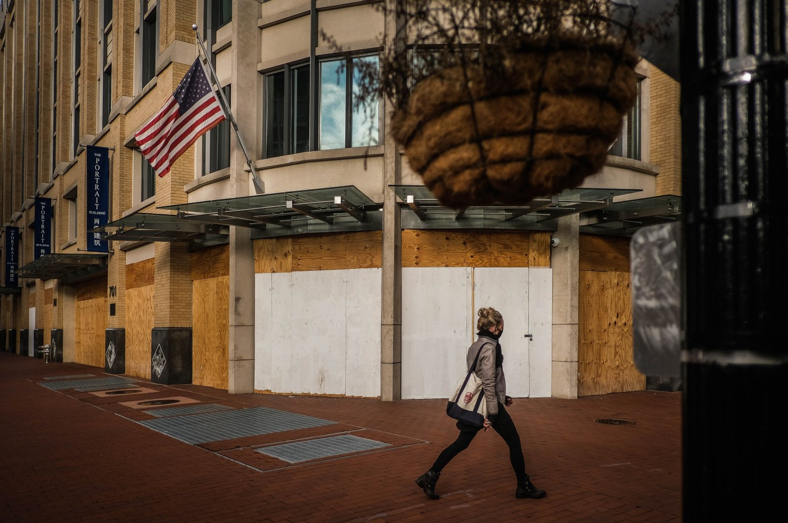 A woman passes by a store protected with wooden boards in Washington, D.C., U.S., Nov. 1, 2020. (EPA-EFE Photo)