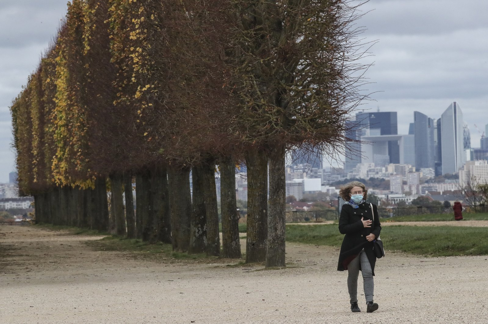 A woman wearing a mask as a precaution against the coronavirus walks through the garden of Saint-Germain-en-Laye, west of Paris, Nov. 2, 2020. (AP Photo)