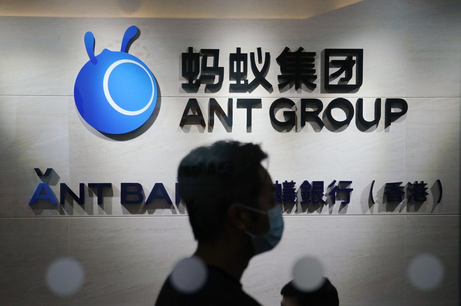 An employee walks past a logo of the Ant Group at their office in Hong Kong, China, Oct. 23, 2020. (AP Photo)