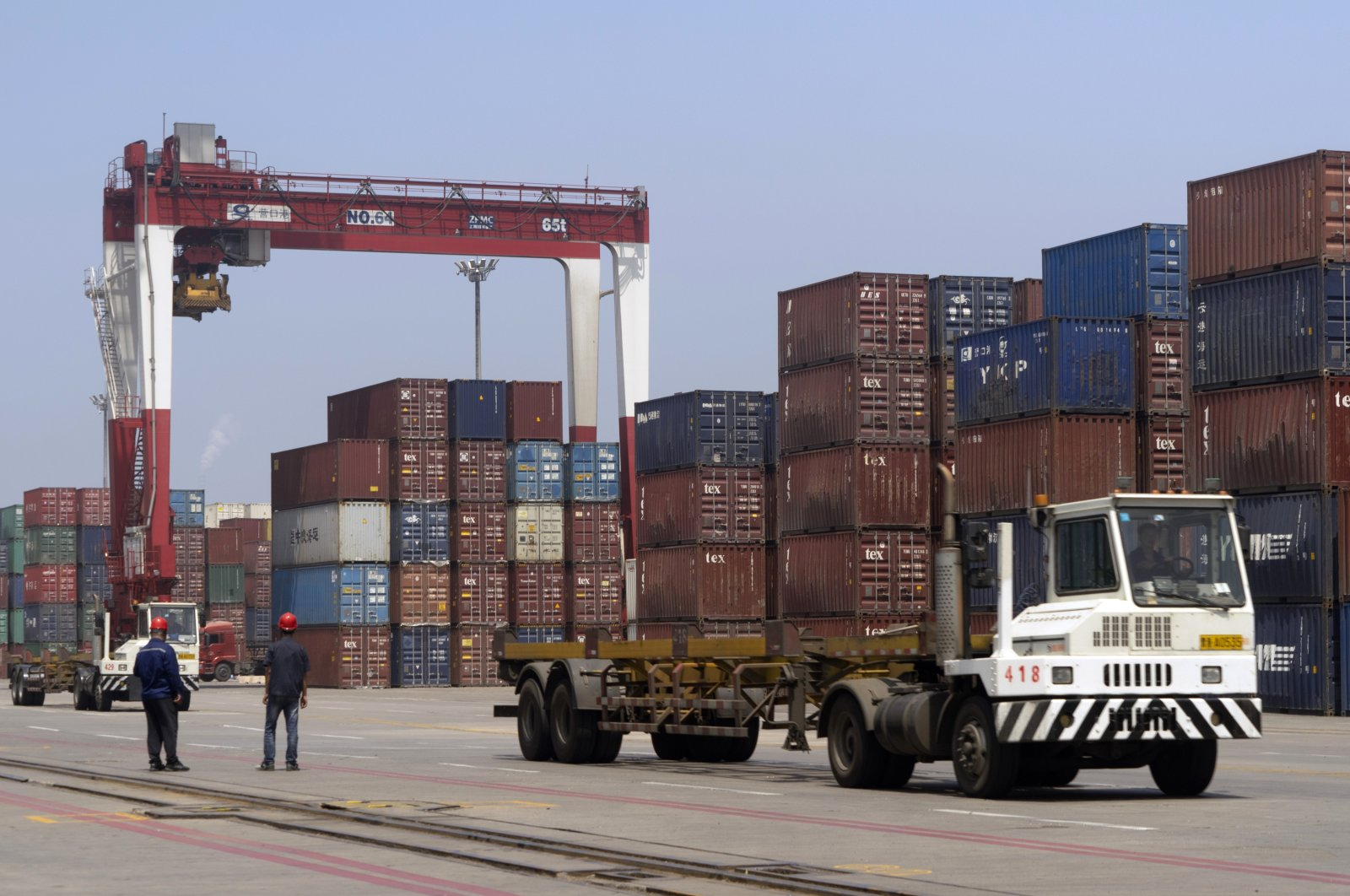 Workers watch as a truck passes by stacks of shipping containers at a port in Yingkou in northeastern China's Liaoning province, July 24, 2019. (AP Photo)