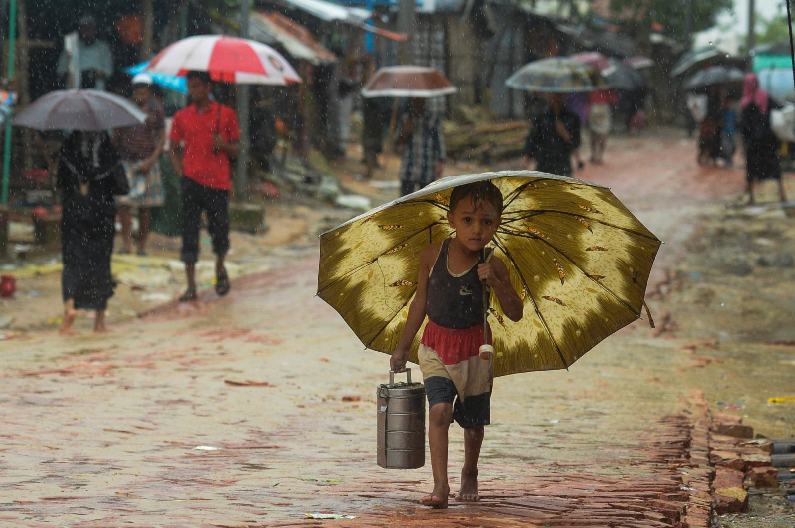 A Rohingya refugee boy shelters under an umbrella as he makes his way during a monsoon rainfall at Kutupalong refugee camp in Ukhia, Cox's Bazar, southeastern Bangladesh, Sept. 12, 2019. (AFP)