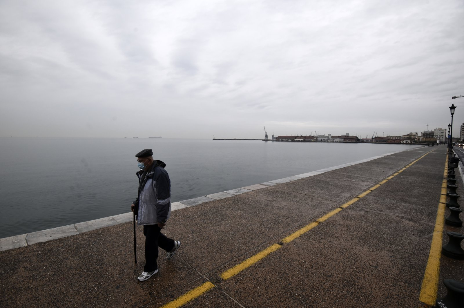 A pedestrian wearing a mask against the spread of COVID-19 walks on a coastal avenue during the lockdown in the northern city of Thessaloniki, Greece, Nov. 3, 2020. (AP Photo)