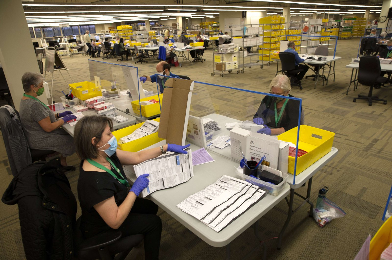 King County Elections worker Nora Al Gwahery (bottom), opens ballots at the King County Elections headquarters on November 3, 2020 in Renton, Washington. (AFP Photo)
