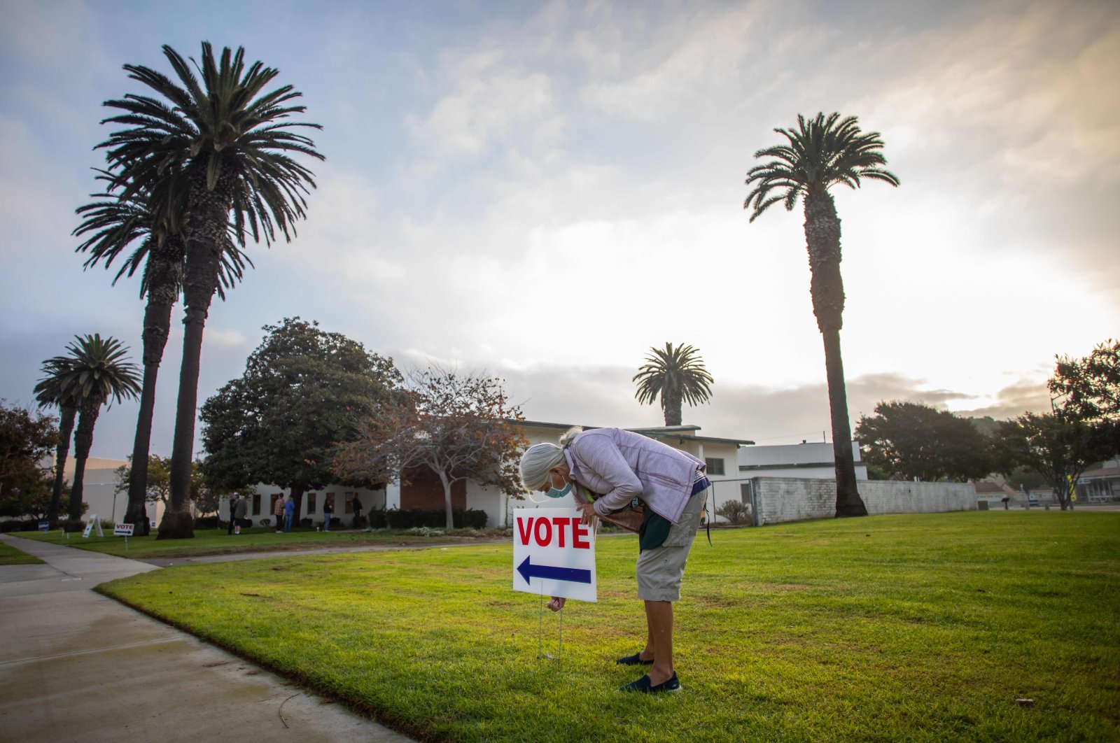 Lorraine Crawford puts vote signs as the sin rises the Main Street Branch Library vote center on November 3, 2020 in Huntington Beach, California. (AFP Photo)
