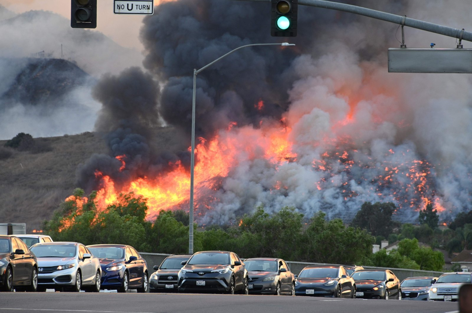 Flames are seen in the background as vehicles drive on a highway overpass at the Blue Ridge Fire in Chino, California, Oct. 27, 2020. (AFP Photo)