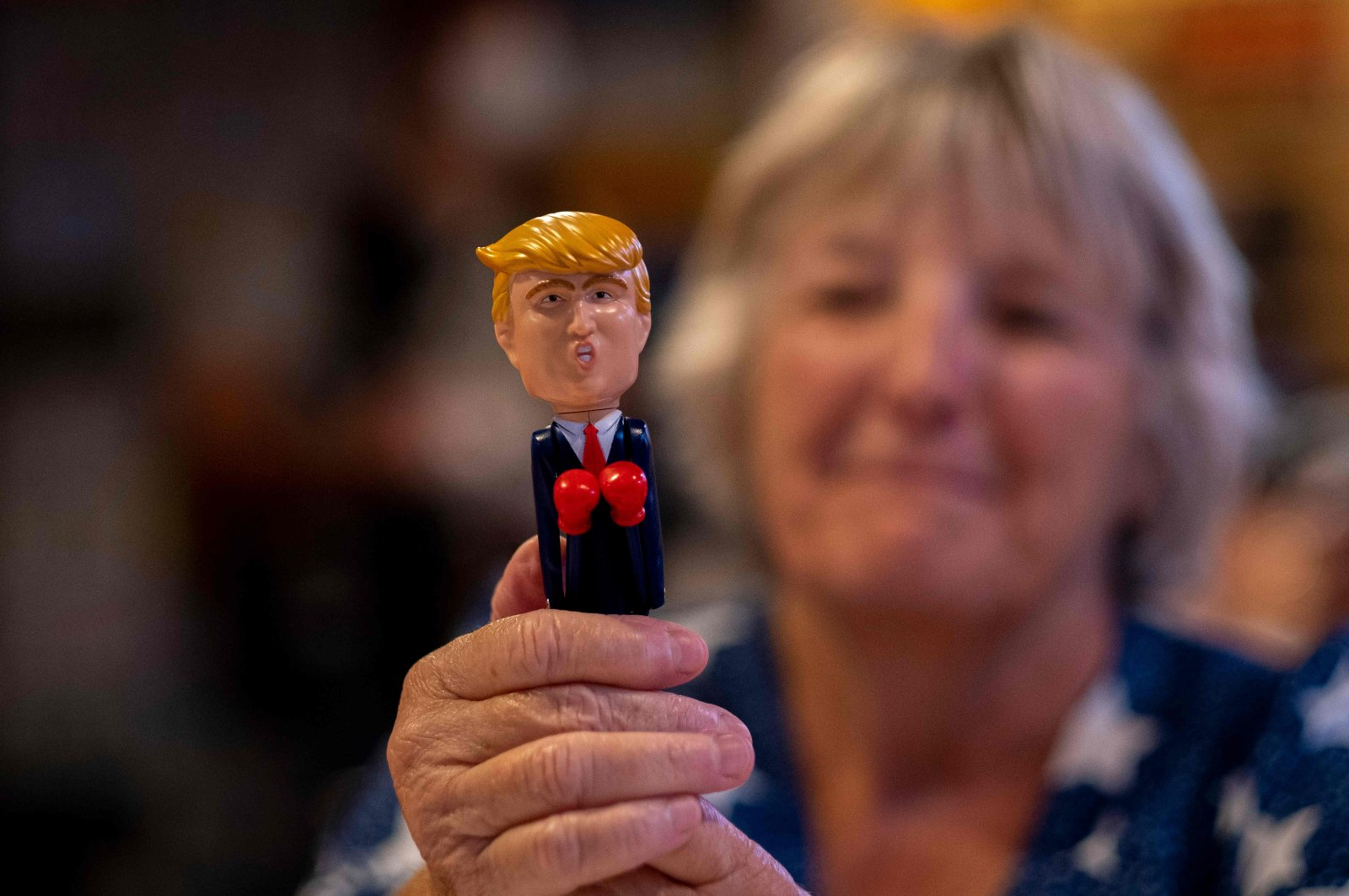 """A woman shows a Donald Trump boxing figurine at an election night watch party organized by the group """"Villagers for Trump"""" in The Villages, Florida, on November 3, 2020. (AFP Photo)"""