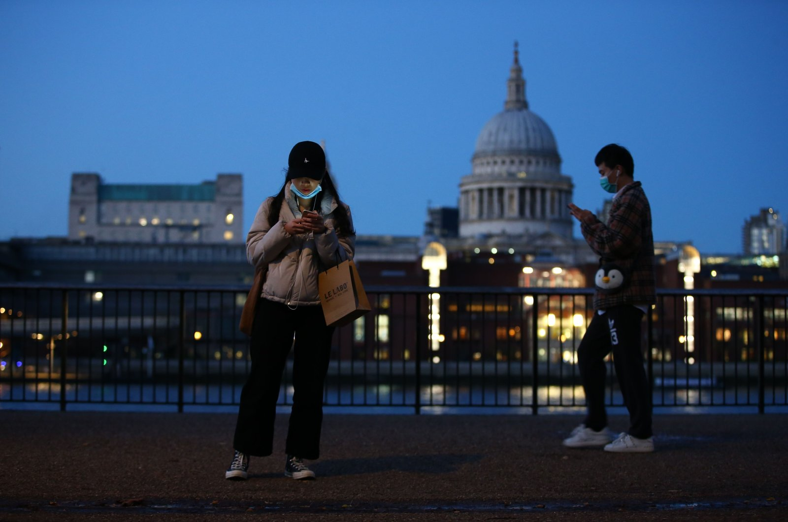 Pedestrians wearing masks because of the coronavirus pandemic walk by the River Thames with St. Paul's Cathedral in the background as the U.K. prepares to head into a second coronavirus lockdown in an effort to combat soaring infections, central London, Nov. 3, 2020. (AFP Photo)