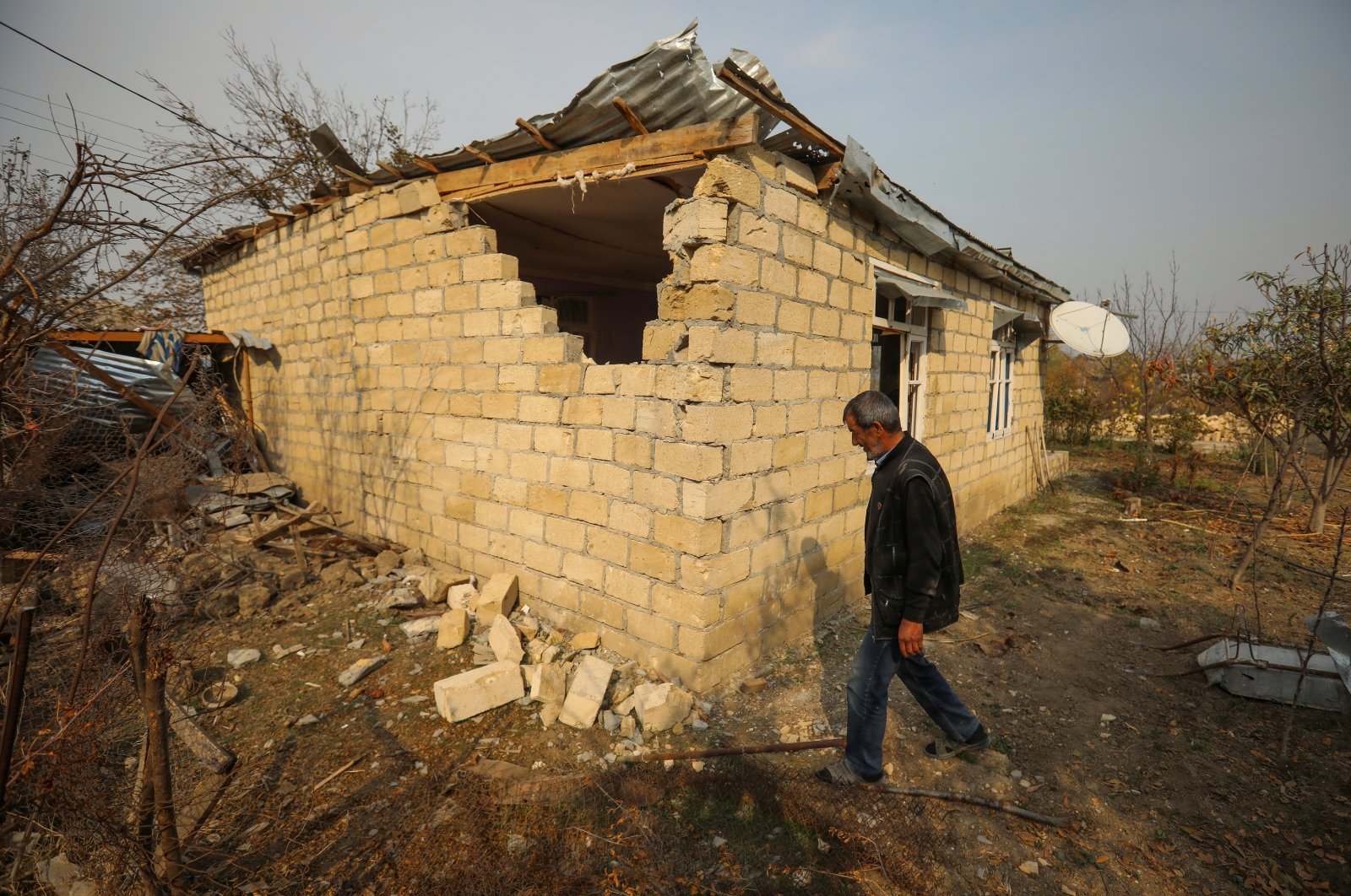 A local resident walks next to his house that was damaged by recent Armenian shelling in the city of Tartar, Azerbaijan, Nov. 2, 2020. (REUTERS Photo)