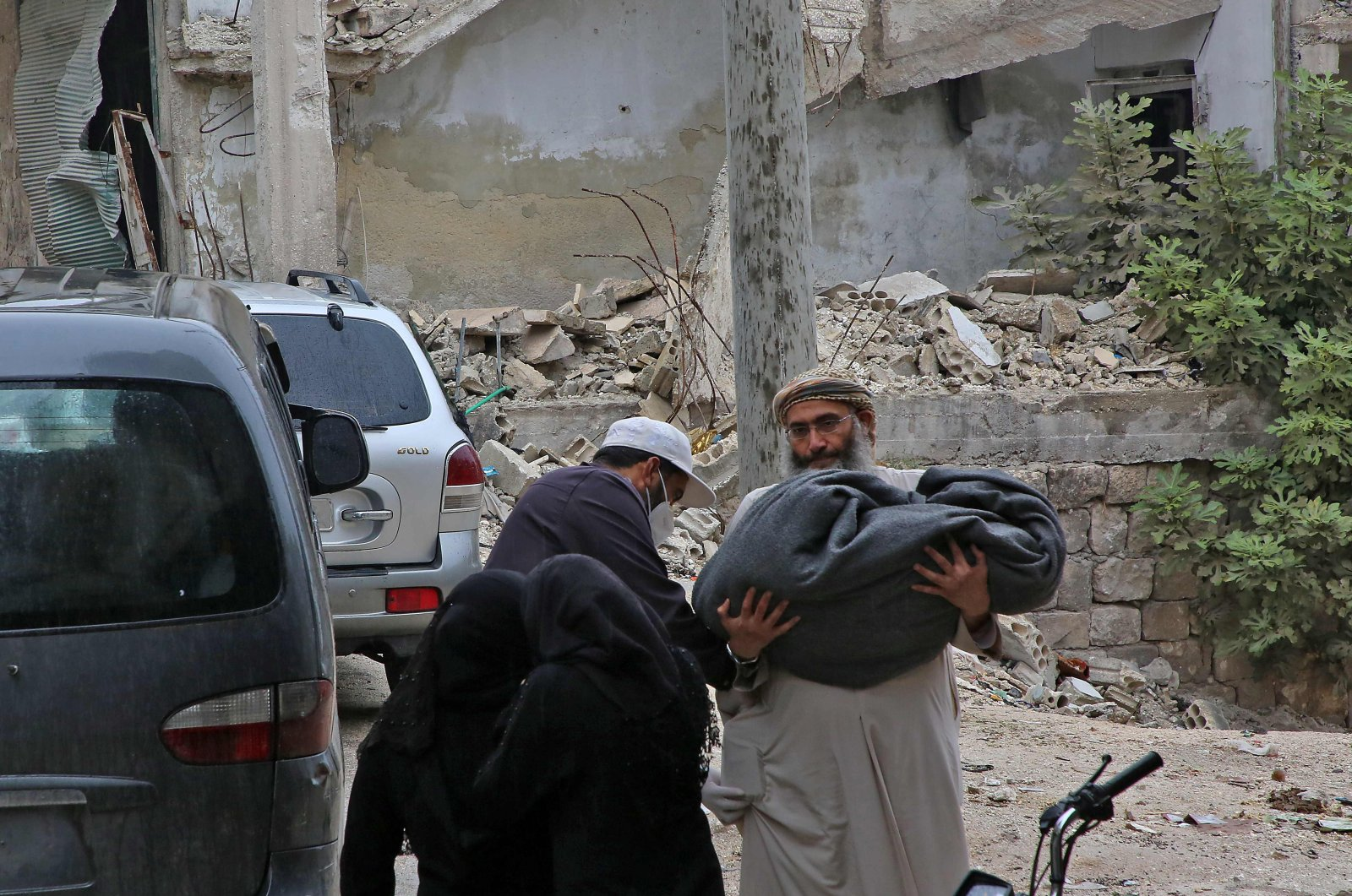 A Syrian man carries the body of a child killed in early morning shelling on the town of Ariha by government forces in the opposition-held area in northwestern Syria early on Nov. 4, 2020. (AFP Photo)